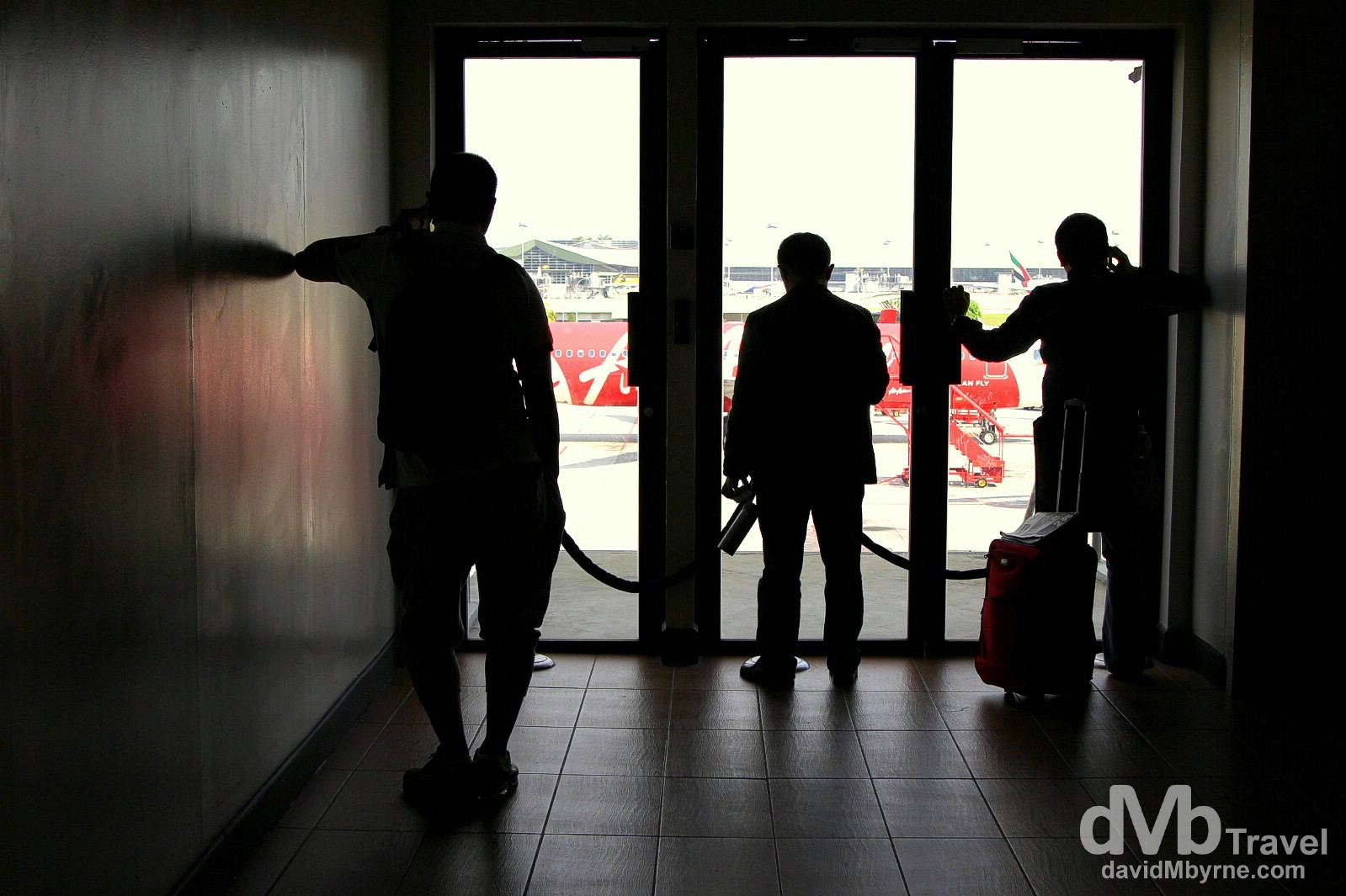 Silhouettes of transit travellers looking out onto the tarmac from the departures terminal of Kuala Lumpur International Airport, Kuala Lumpur, Malaysia. March 6th 2012.
