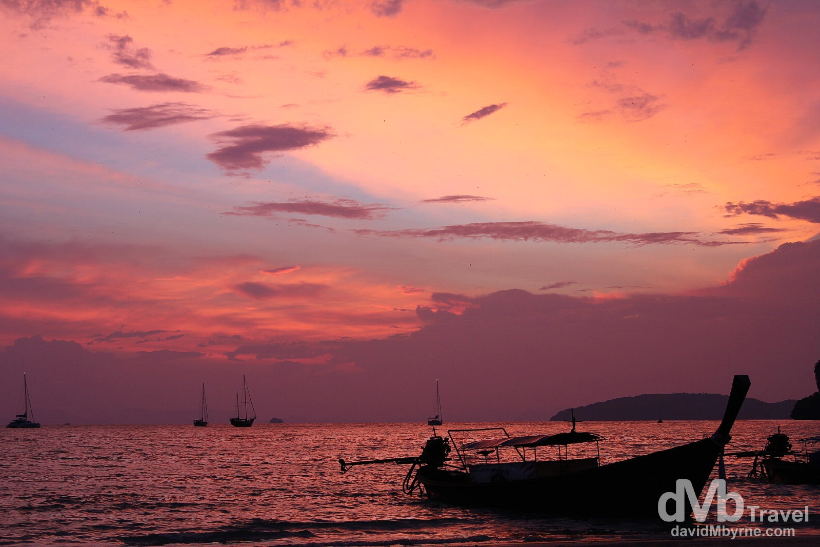 The sunset I witnessed on the last night by the beach in southern Thailand, and Thailand itself, wasn't one of those bright-golden-disc-in-the-sky type of sunsets - the sun disappeared behind clouds well before it hit the horizon & things dimmed pretty fast after that. I was disappointed – 3 nights & 3 sunset no-shows. But then, sitting as I was sulking into my Chang beer & cursing all things Thailand, something wonderful happened; the sky above started to glow a beautifully comforting shade of pink. This continued until eventually everything around was bathed in this beautiful pinky purple glow. It was surreal & sitting on a beach awash with pink was very zen. Late sunset on Hat Rai Leh West Beach Krabi Thailand