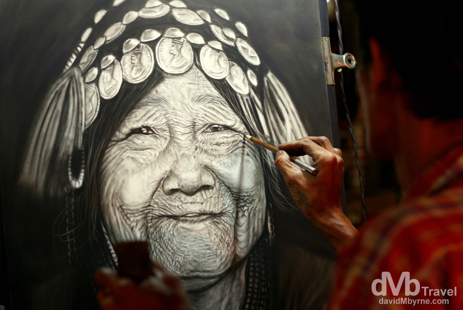 An artist putting the final touches to a piece of work in the Night Market, Chiang Mai, northern Thailand. March 9th 2012.