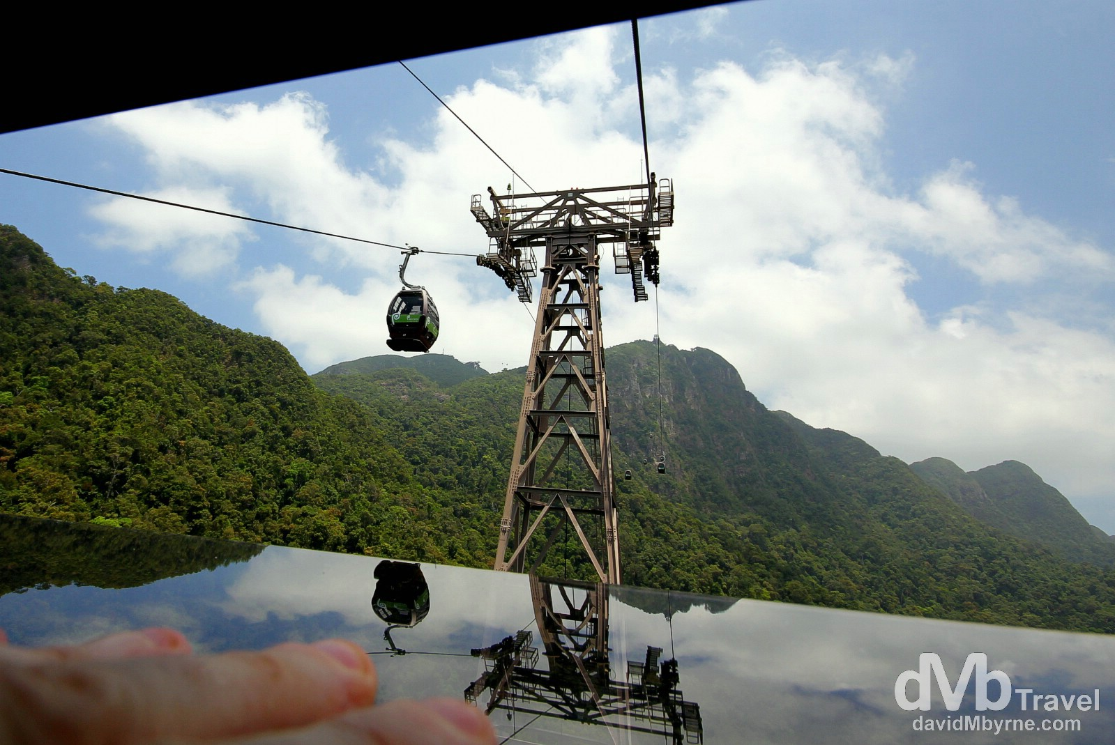 This is a picture taken through a narrow cap in a window of the Langkawi Cable Car, the most popular tourist attraction on the island. I was ascending when I took this & needed to keep the spring-mounted window open with my left hand (bottom left) while holding the camera with my right. I'm a sucker for reflections so of course I particularly like the reflections seen here; I feel they detract from the poor mountain visibility caused by low-lying haze emanating from, I assume, the jungle floor below. In the distance, beyond the mammoth 70m-high Tower 2 as seen here, is the longest free span section of the whole 2.2km cable car ride, the 950m stretch between the tower up to the Middle Station. Gunung Machinchang, Langkawi Island, Malaysia. March 22nd 2012.