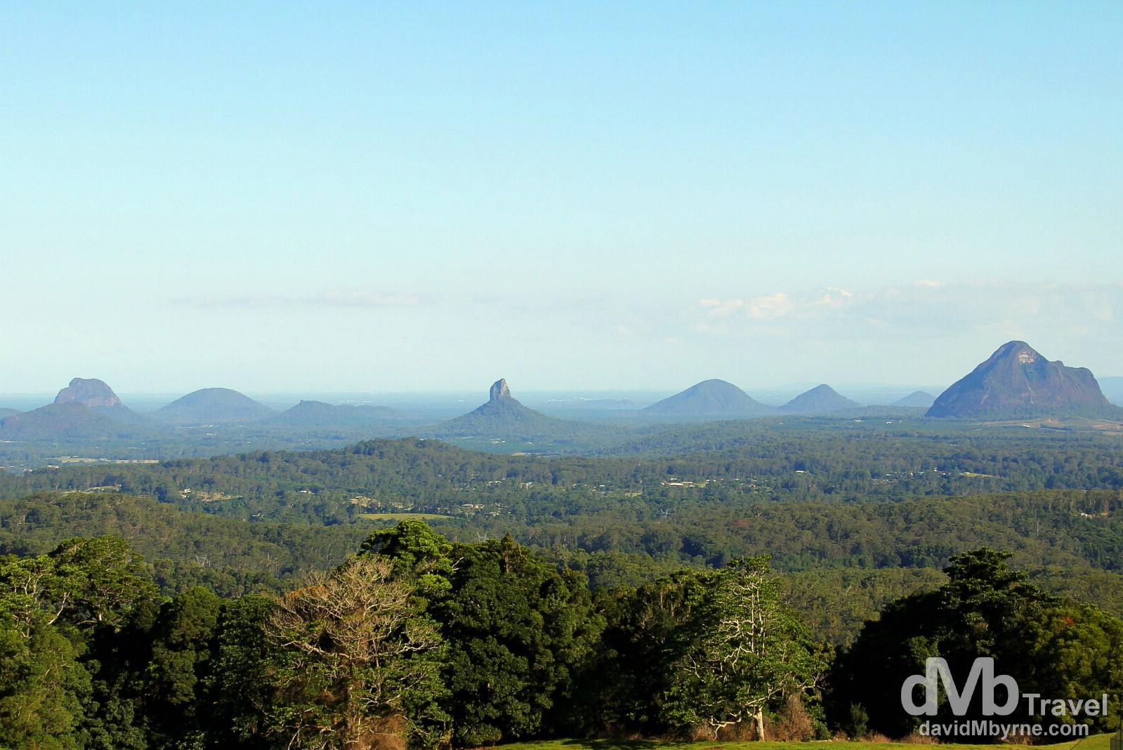 The Glass House Mountains as seen from a lookout in the Mary Cairncross Reserve. The mountains are a group of eleven hills, volcanic plugs of hard alkali rhyolite, that rise abruptly from the coastal plain, the results of ancient volcanic activity some 27 million years ago. They are not all that high - the highest mountain, Mount Beerwah, is only 556 metres above sea level - but shrouded in mist they, and the plain they sit on, are a beautiful sight. The mountains were named by explorer Captain James Cook on 17 May 1770 as the peaks reminded him of the glass furnaces in his home county of Yorkshire. Queensland, Australia. April 4th 2013.