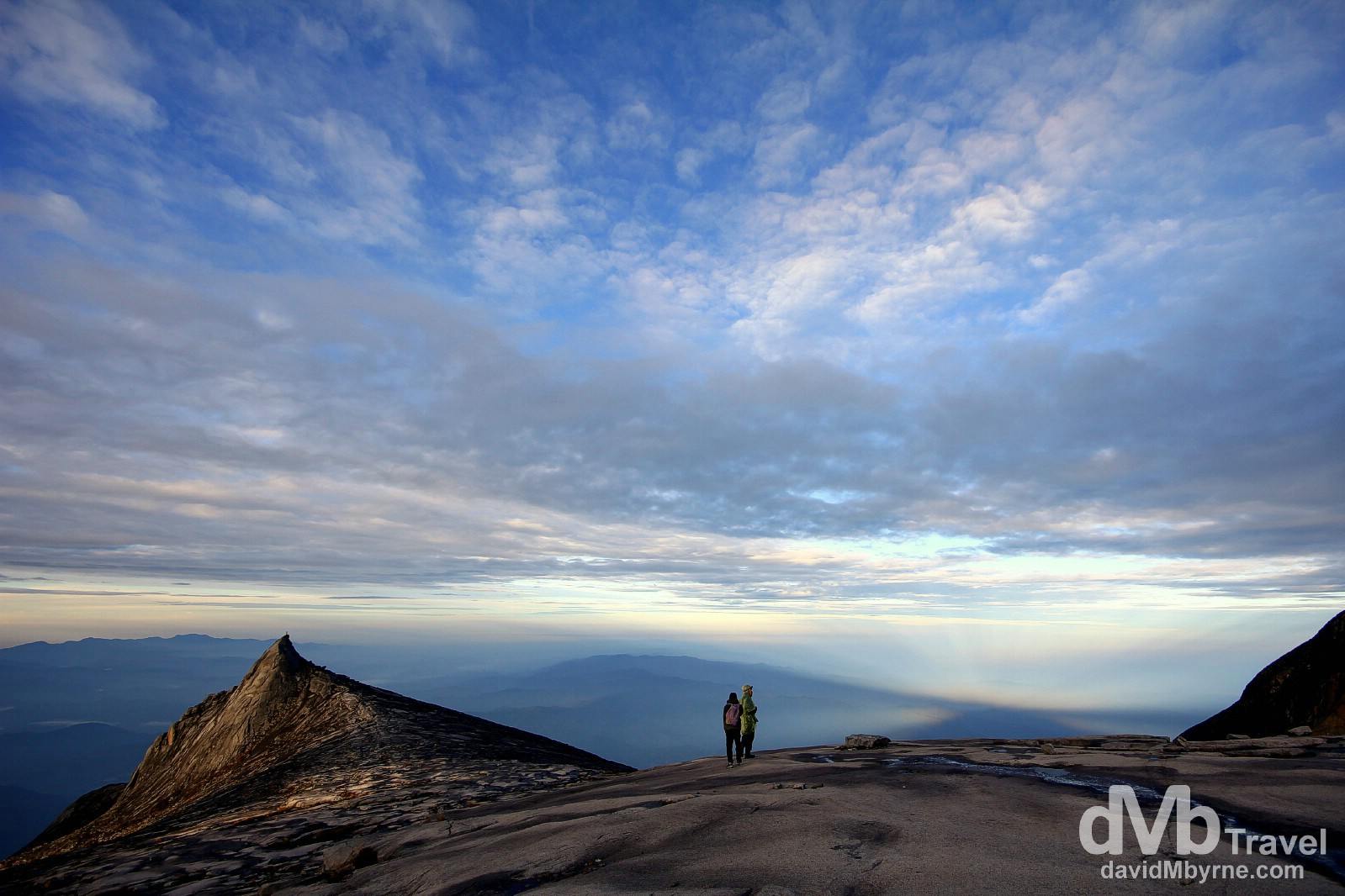A picture captured on the descent of climbers admiring the post sunrise view over Sabah, Malaysian Borneo, from the granite expanse leading to the summit of Mount Kinabalu. The views of Sabah from this height, stretching out below in all directions, are phenomenal. June 23rd 2012.
