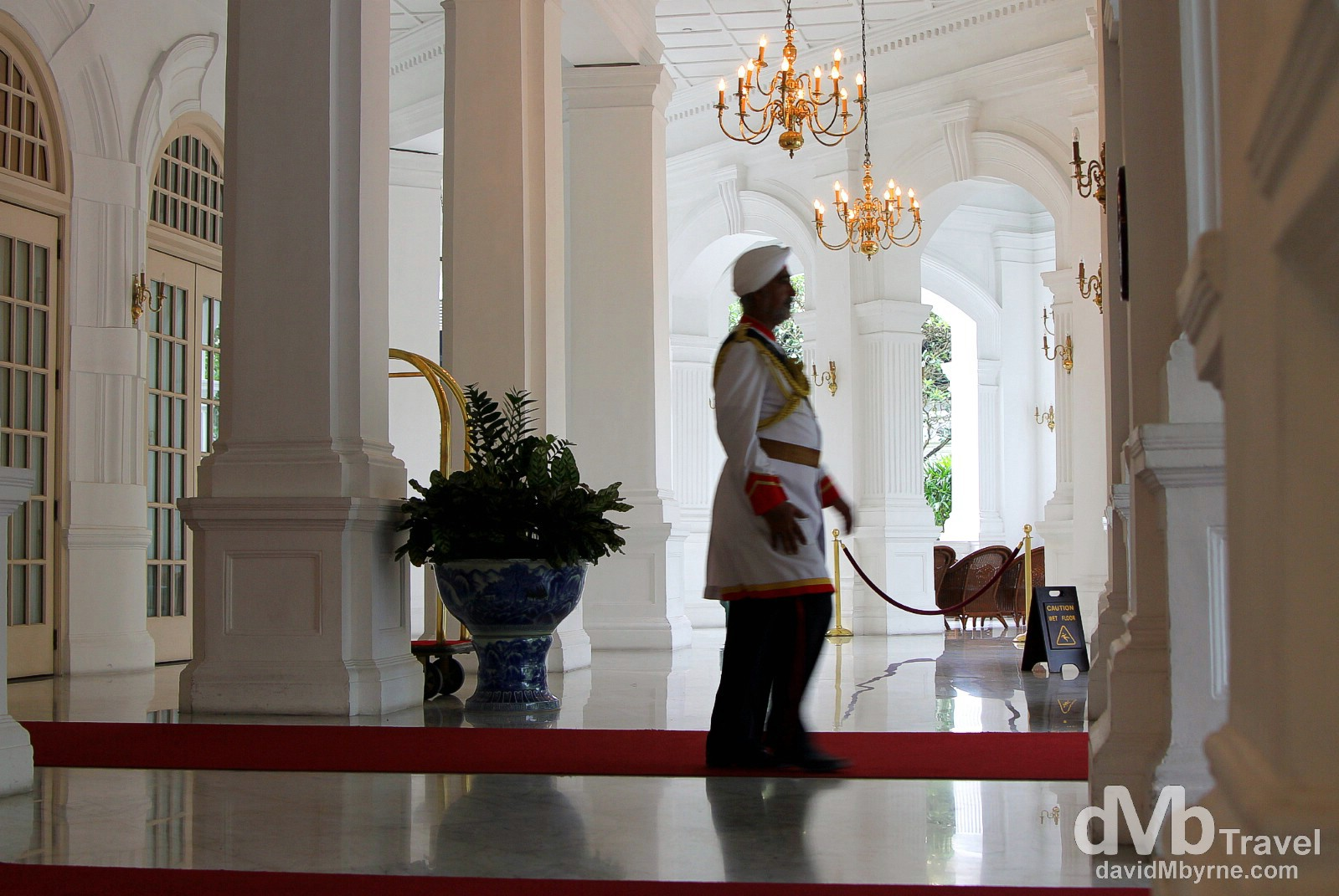 A doorman at the lobby entrance to Raffles Hotel, Singapore. A Singaporean institution & colonial opulence personified, the regal Raffles Hotel opened as a modest 10-room bungalow in 1887 with the main building following in 1889. By the 1970's it had seen better days & was a shabby relic of its old, glamorous self. A major revamp in time for a 1991 reopening brought it back to something resembling its former glory. I spent an hour or so sniffing around and sticking my camera at white walls, arches, fancy gold chandeliers, polished marble floors, & rich people. It was fun. Raffles Hotel, Singapore. March 28th 2012.