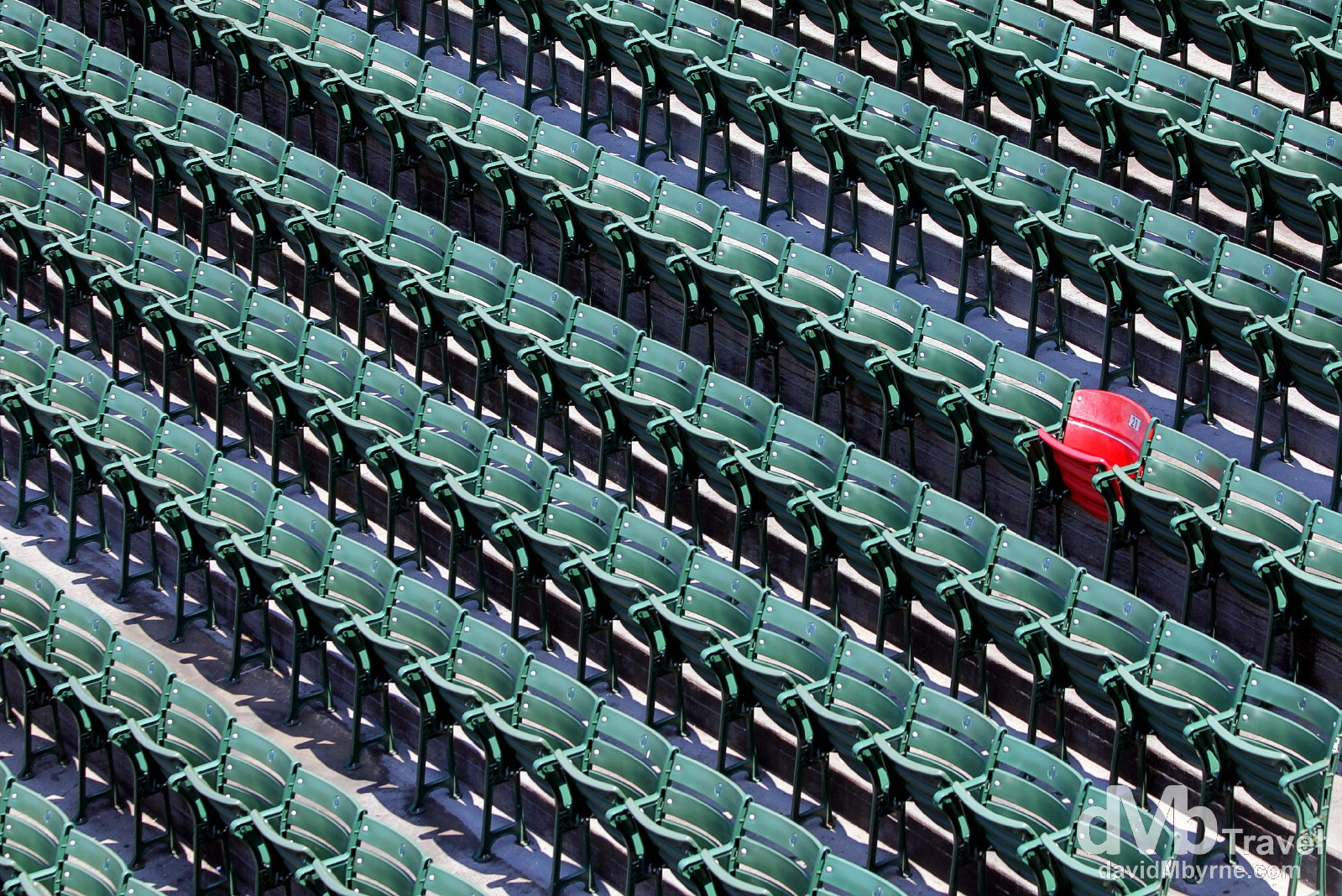 The Ted Williams red seat stands out amongst a see of green in the right field bleacher section of Fenway Park. Many baseball greats have played for the Red Sox, among them Babe Ruth, Carl Yastrzemski, & Ted Williams. On June 9, 1946, Williams hit a 502-foot homerun, the longest ever hit into the Fenway bleachers. The seat, located in section 42, row 37, seat 21, was painted red, one of only 2 in Fenway, to commemorate Williams' titanic blast, although at the time of the home run the bleachers were real bleachers and not individual seats. Fenway Park, Fenway, Boston, Massachusetts, USA. July 17th 2013.