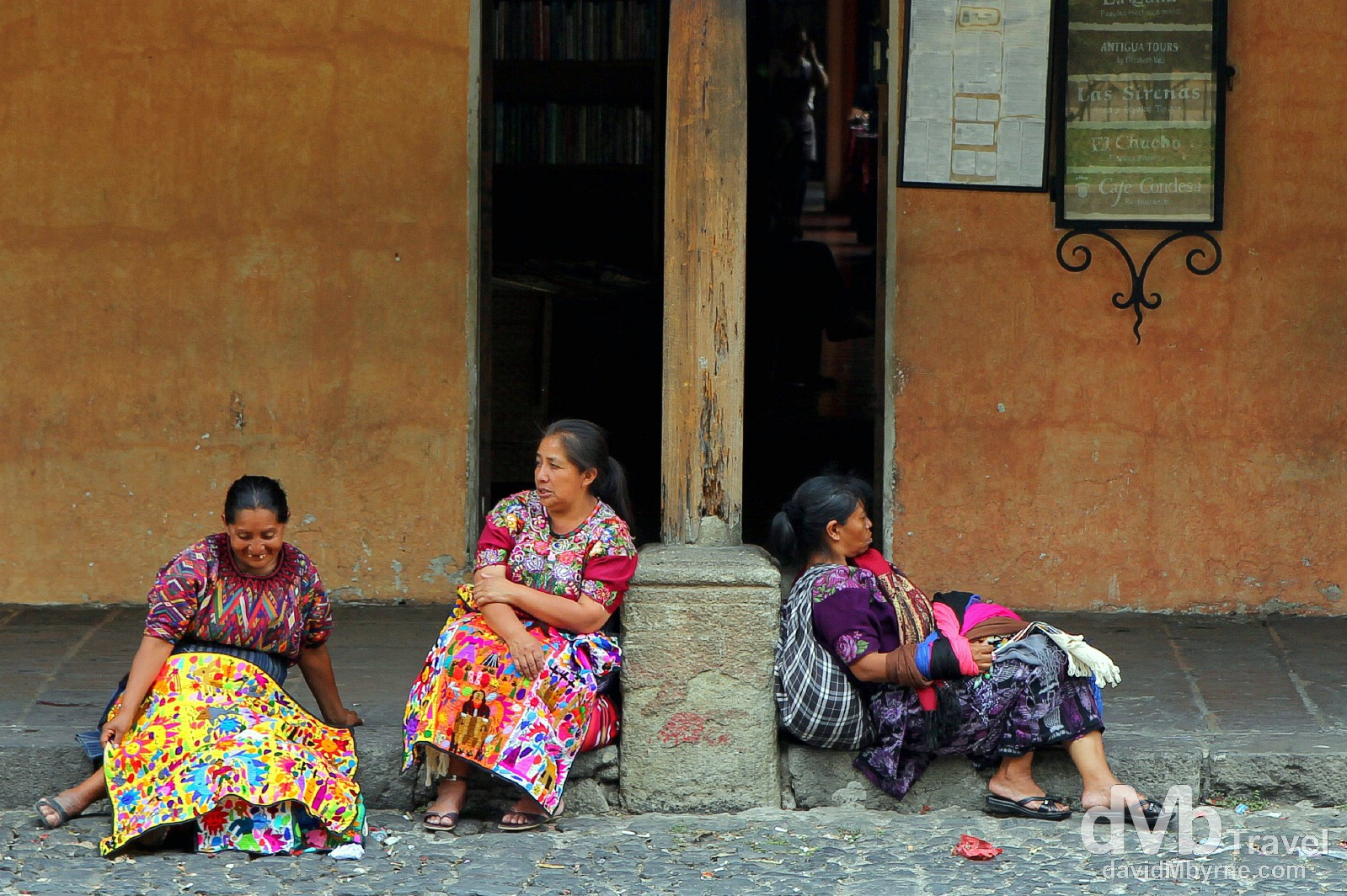 Three Mayan ladies taking a break from peddling their wares by the edge of Parque Central, Antigua, Guatemala. May 19th 2013.