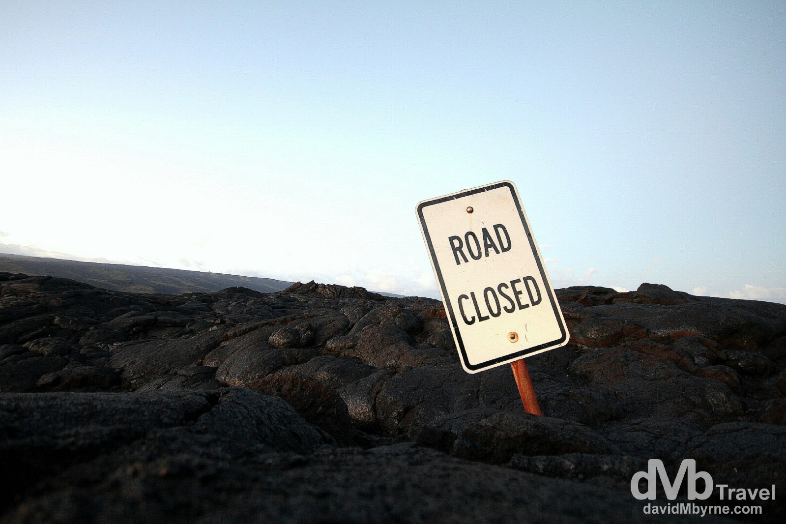 Road closed indeed. A single road sign is all that's left of a road buried in lava on the south coast of The Big Island, Hawaii. March 1st 2013.