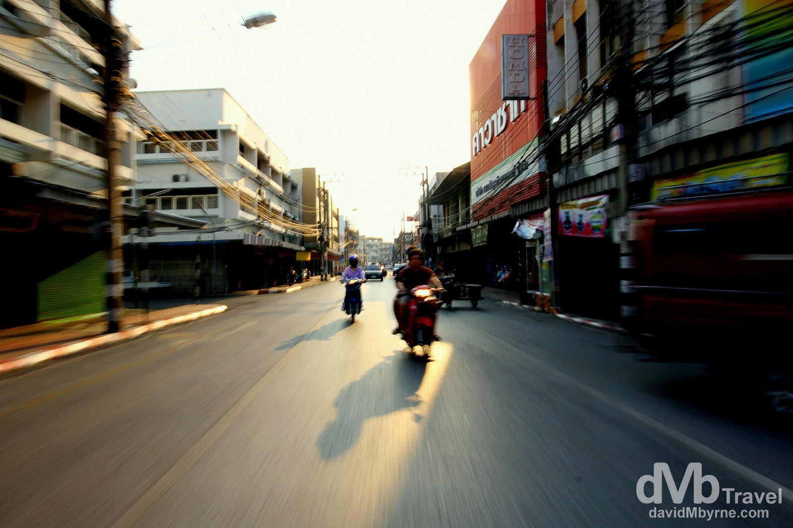Motion & late afternoon shadows as seen from the back of a moving sawngthaew, an open-backed pick-up that doubles as a taxi, on the way to the Chiang Mai bus station to get the bus to Bangkok. March 15th 2012. on the streets of Chiang Mai, northern Thailand. March 15th 2012