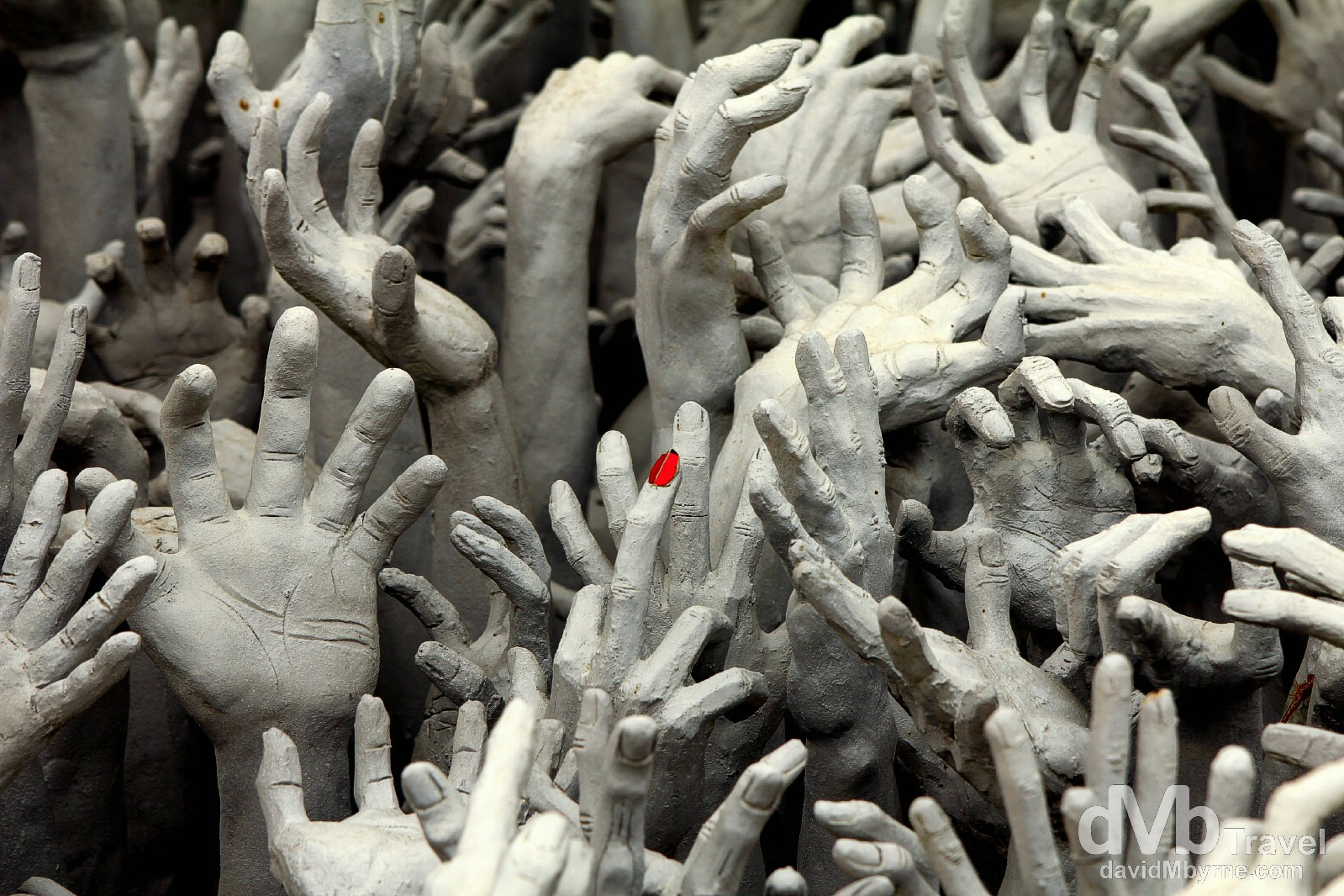 A lone red fingernail stands out in a sea of grey on a sculpture in the grounds of Wat Rong Khun, Chiang Rai, northern Thailand. March 11th 2012.