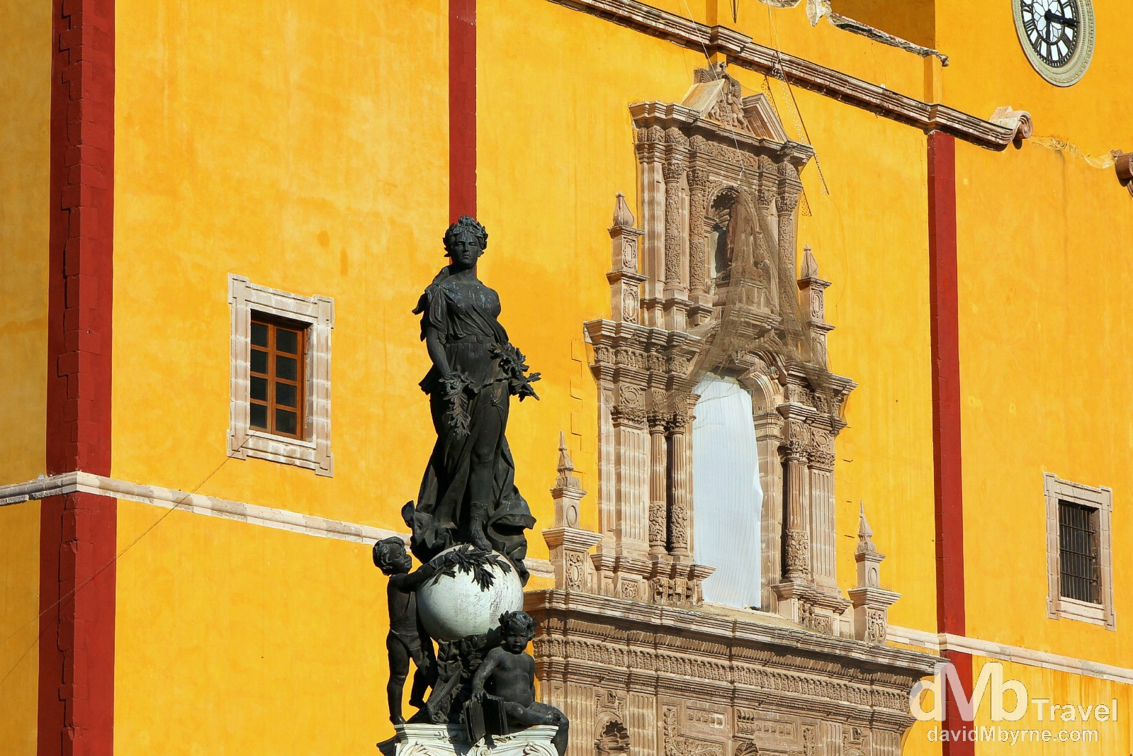 The centre of the modern city of Guanajuato is the Plaza de la Paz (Plaza of Peace), also known as the Plaza Mayor (Main Plaza). Since the colonial period, the richest of the city's families located their main homes here, along with government buildings and the parish church, now a basilica, Basilica de Nuestra Senora de Quanajuato. Built between 1671 to 1696, it houses a 1000-year-old statue donated by Spanish King Charles I in a bid to protect it from the Arab invasion of Spain. The statue fronting the church resides in the centre of the small plaza garden. It's a sculpture of a woman which represents peace; its placement here in the late 19th century caused the official name to change to Plaza de la Paz. Today, the plaza is surrounded by the basilica, other churches, government and commercial buildings, many of which were once mansions. Guanajuato, Mexico. April 22nd 2013.
