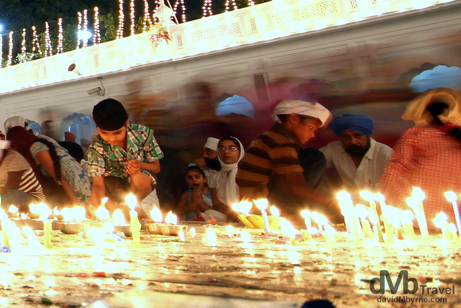 Lighting candles by the edge of the Amrit Sarovar (Pool of Nectar) in the Golden Temple complex, Amritsar, India. October 9th 2012.