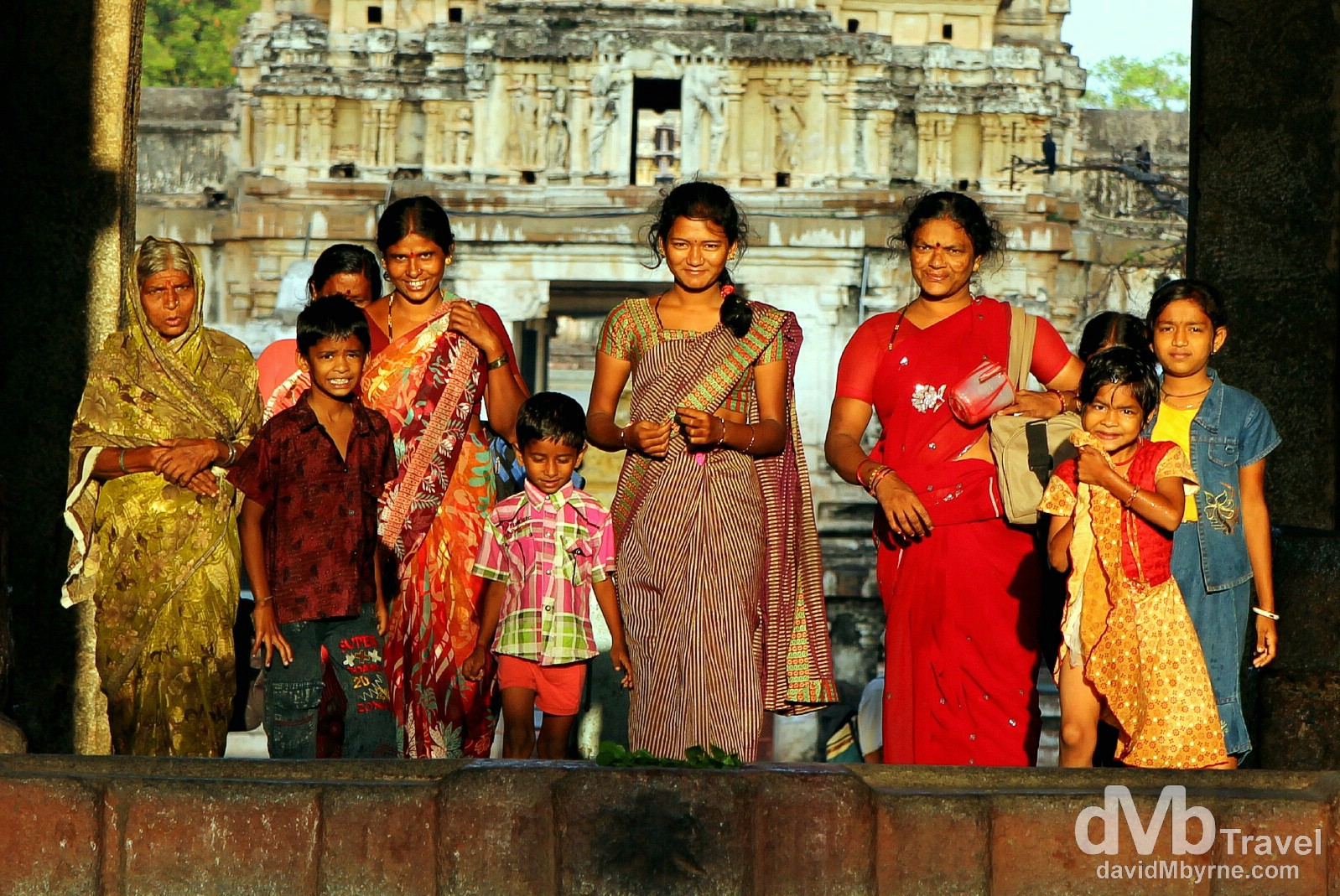 Dawn light illuminates a group of Indians exiting the Virupaksha Temple in Hampi, Karnataka, India. September 24th 2012.