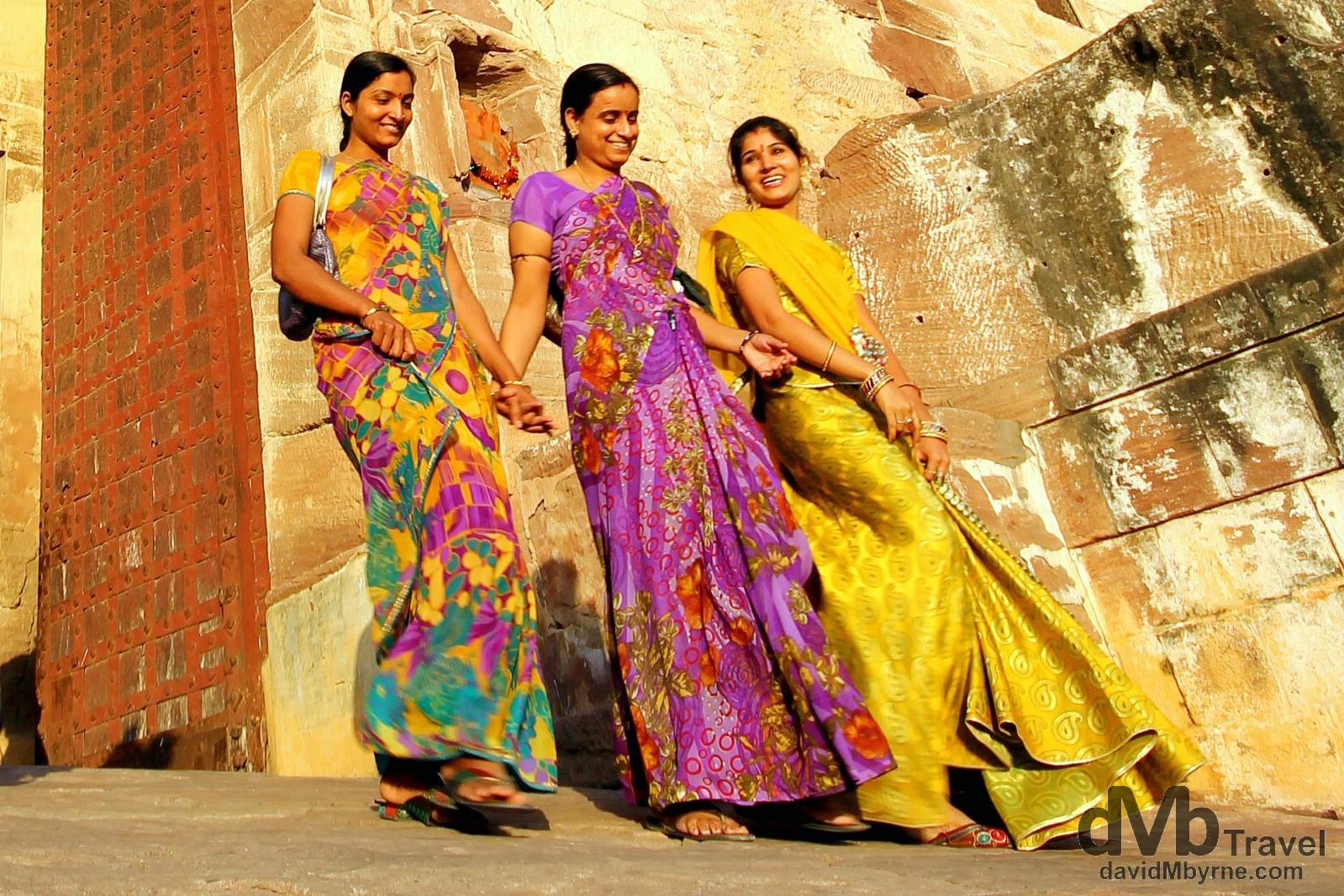 Late afternoon sunlight illuminates three ladies exiting the Mehrangarh Fort in Jodhpur, Rajasthan, India. October 6th 2012.