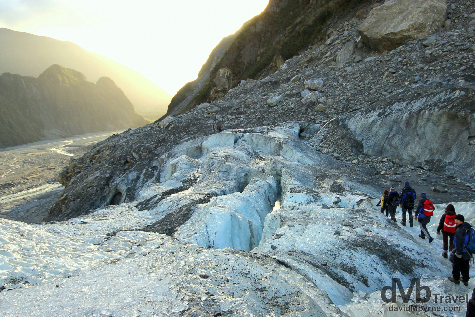 A guided party descending the Fox Glacier as late afternoon sunlight bathes the valley below. Fox Glacier, South Island, New Zealand. May 19th 2012.