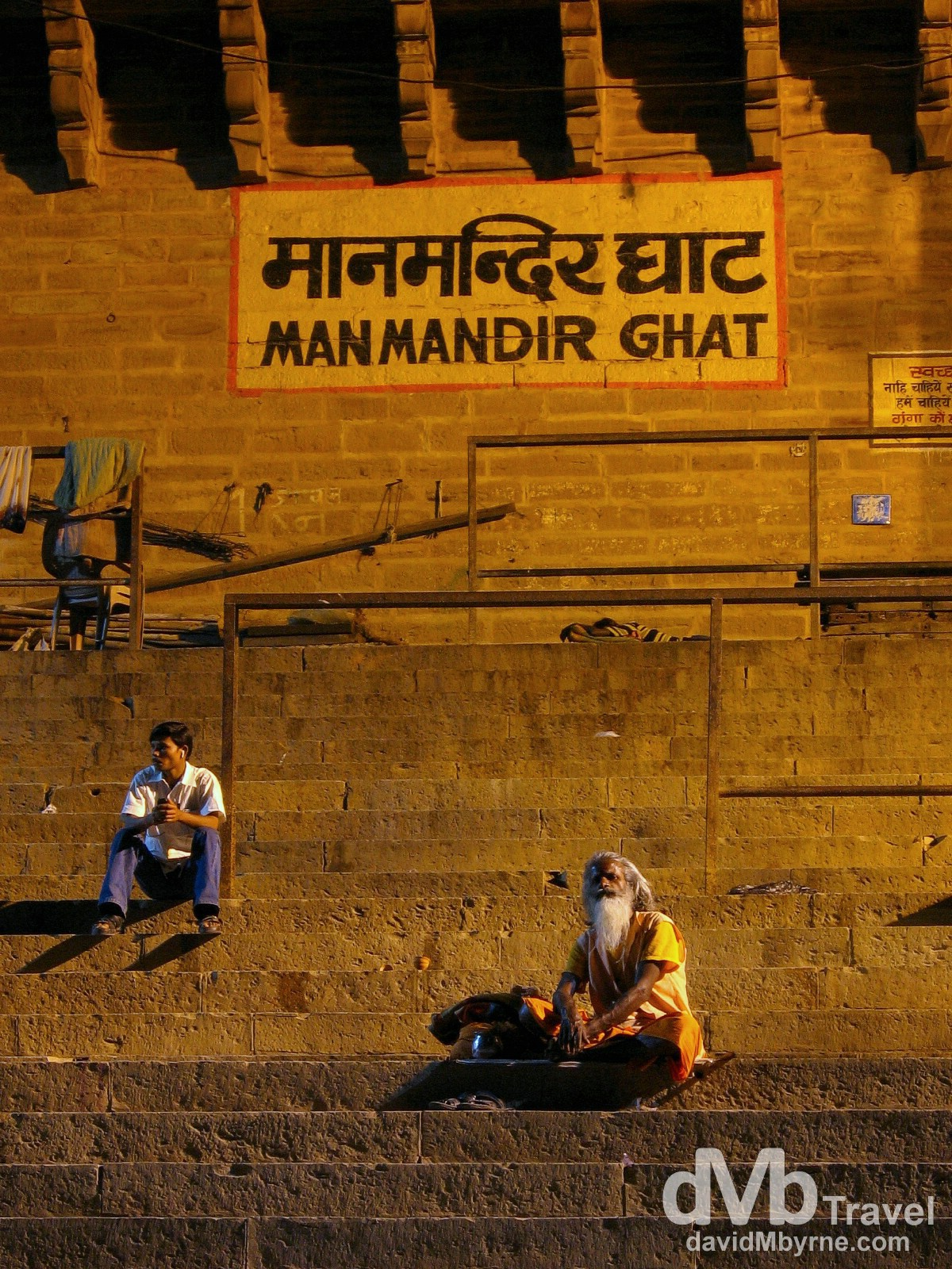 A Sadhu, a Hindu holy man on the path to enlightenment, and a local sitting at Manmandir Ghat, Varanasi, India. Ghats have been used in India for centuries, primarily for worship, but also for bathing and washing clothes. They are also used for the final ritual of cremation and some of Varanasi's Ghats are solely used for this purpose. March 18th 2008.