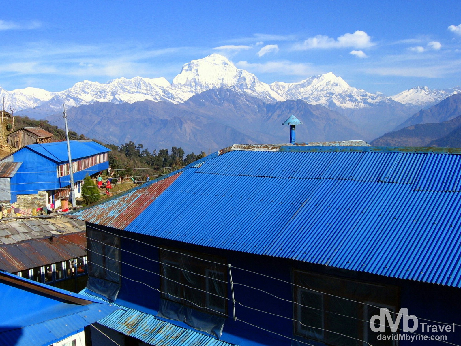 The distinctive blue galvanised roofs of the buildings of Ghorepani village, Nepal. The village sits 1,500ft, 450 metres below Poon Hill and the sight of Dhaulagiri (27,000ft, 8,167m) behind the village makes a spectacular backdrop. Ghorepani Village, Annapurna Conservation Area, Nepal. March 12th 2008.