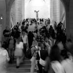 This picture epitomizes the Louvre; busy, grand and classy. It shows the approach to the Italian Renaissance and Grand Gallery section of the Denon wing. In the distance is one of the most celebrated sculptures in the world, the Winged Victory of Samothrace, a second century BC marble sculpture of the Greek goddess Nike, a.k.a. Victory. The Louvre, Paris, France. August 19th 2007.