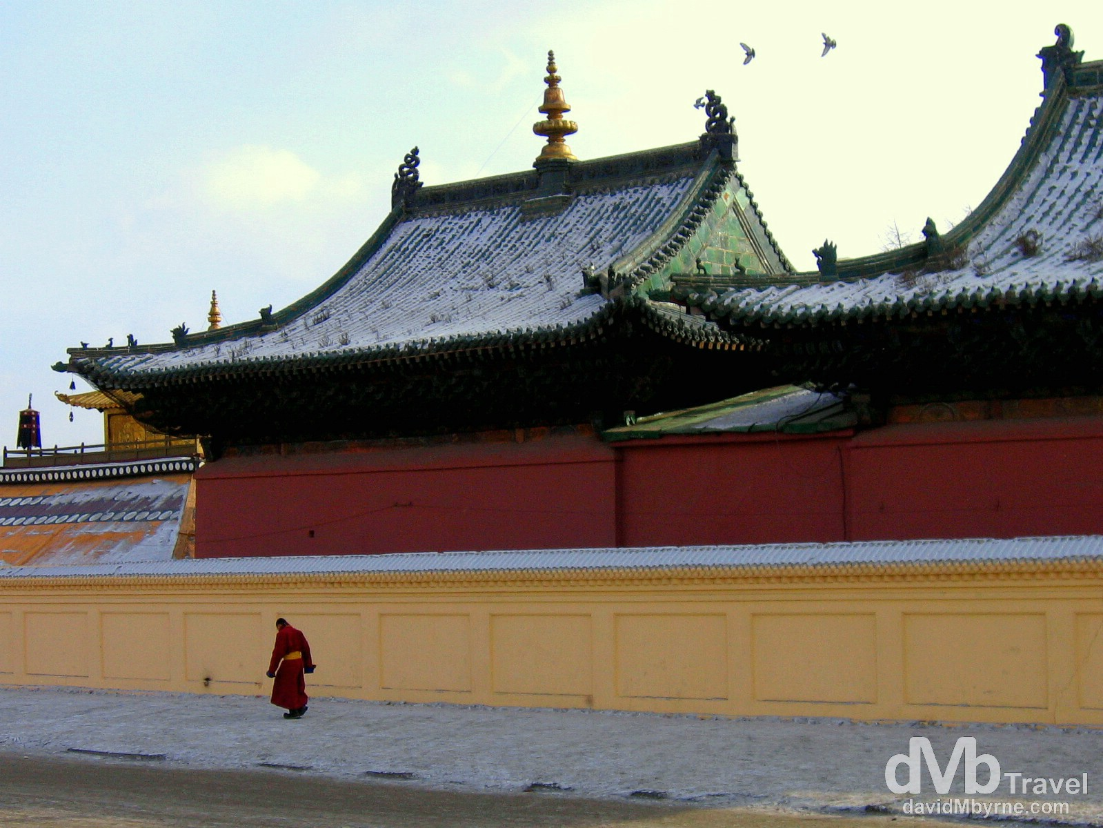 A lama (Buddhist monk) walks past the walls of the Ochirdary Sum (temple) in the grounds of Gandantegchinlen Khiid (monastery), Ulan Batar, Mongolia. February 15th 2006.