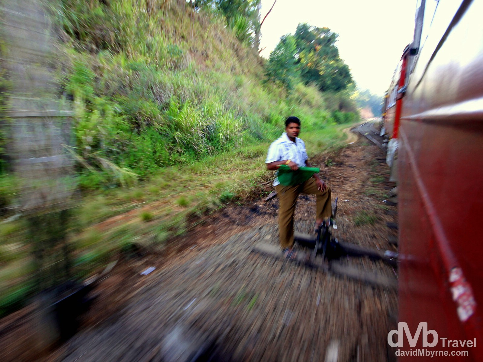 Speeding past a signal operator on the Badulla to Colombo train in central Sri Lanka. September 5th 2012.