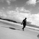 A surfer walking on the beach in Tawharanui Regional Park, North Island, New Zealand. April 28th 2012.