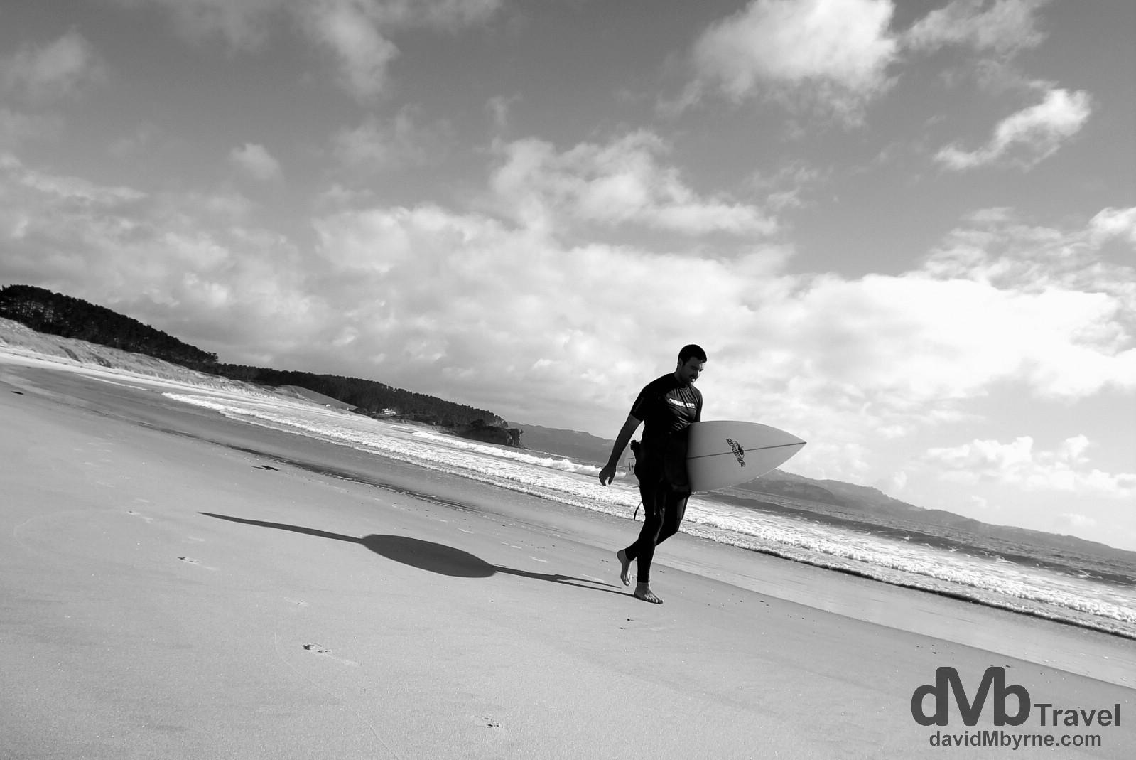 A surfer walking on the beach in Tawharanui Regional Park, North Island, New Zealand. April 28th 2012.