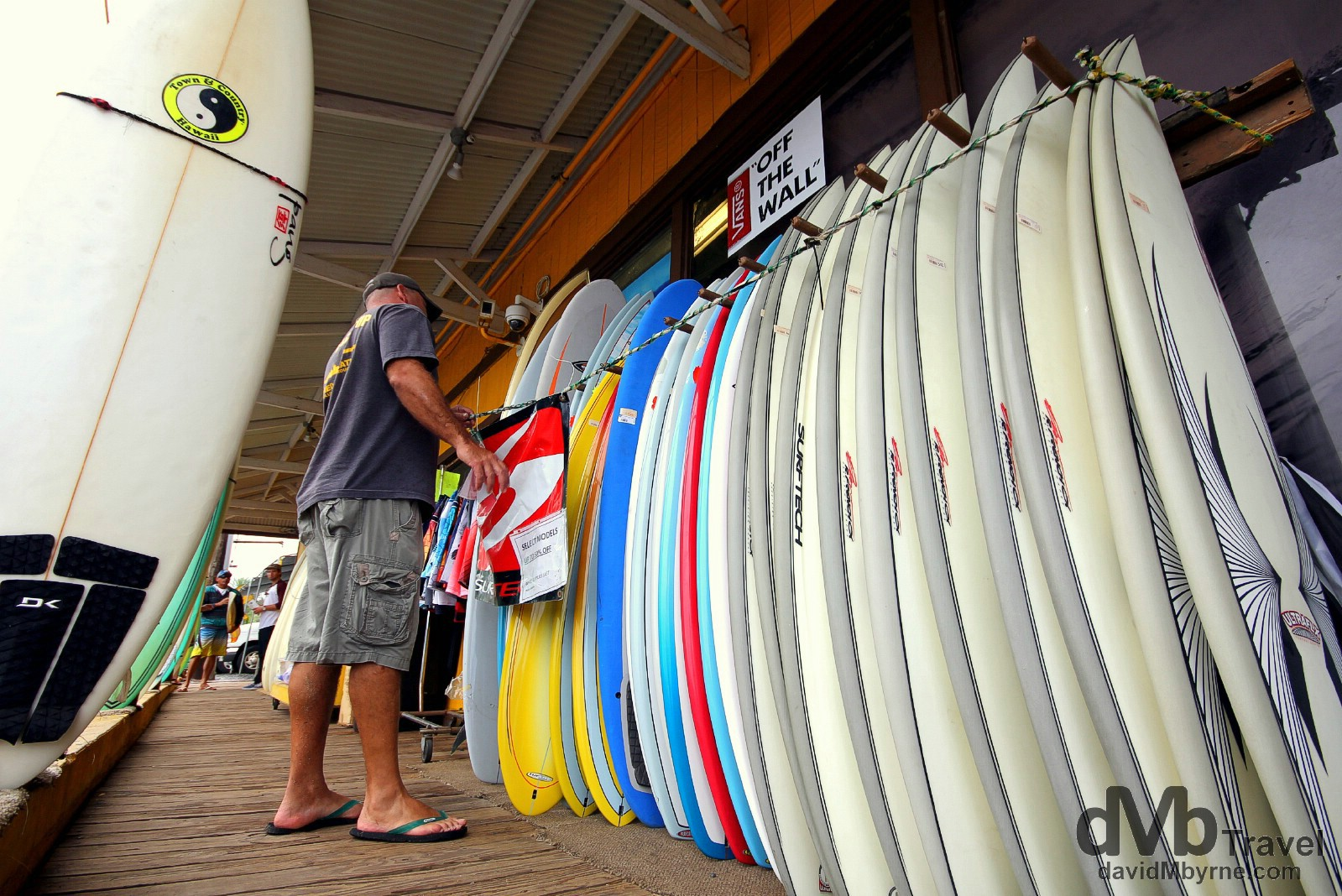 Looking at surf boards outside Surn N Sea, one of the most famous surfing shops in the world. Haleiwa, North Shore, Oahu, Hawaii. March 10th 2013.