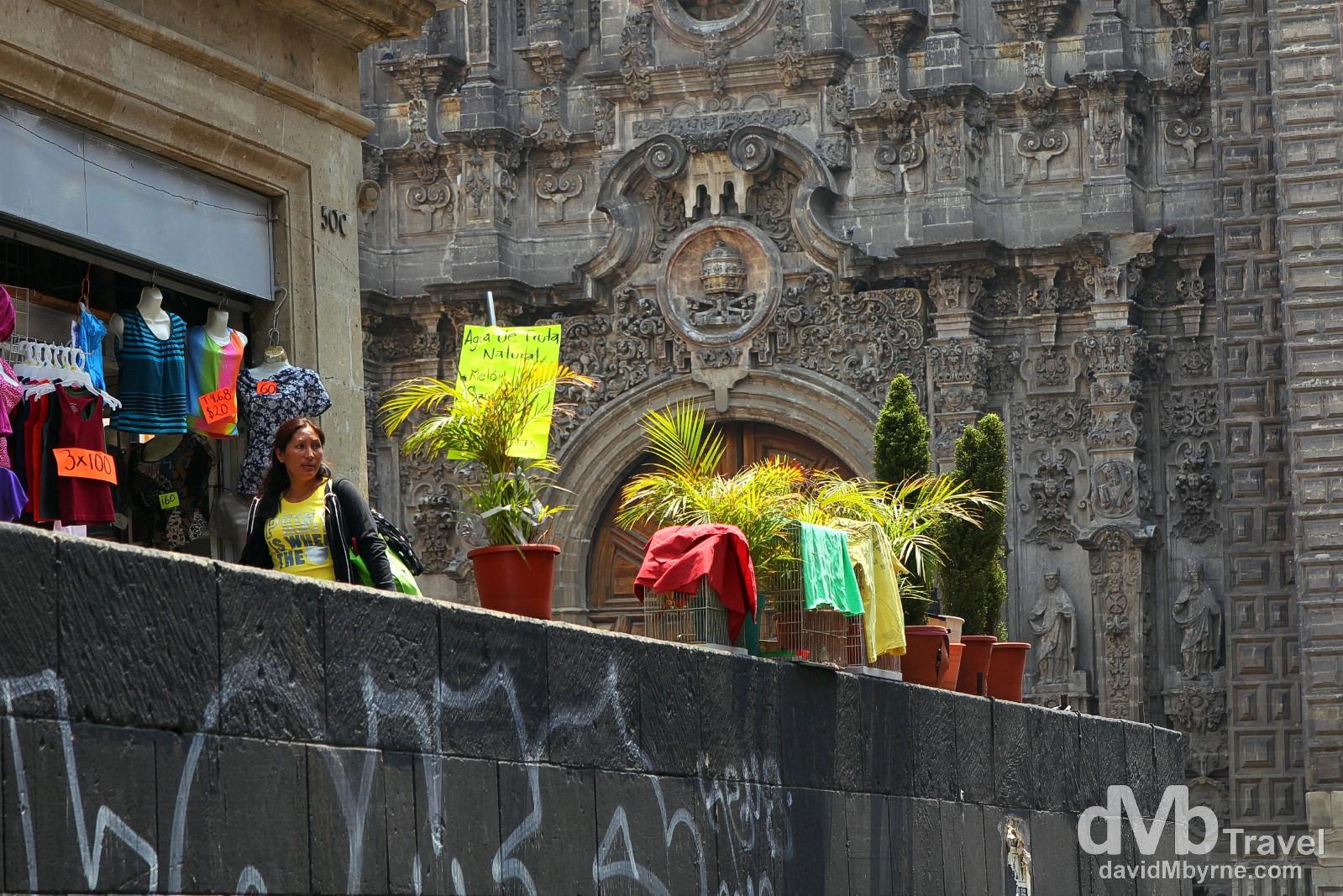 The hyper-baroque façade of Templo de la Santisima Trinidad, graffiti & clothes for sale as seen from Mondea, Central Mexico City. April 26th 2013.
