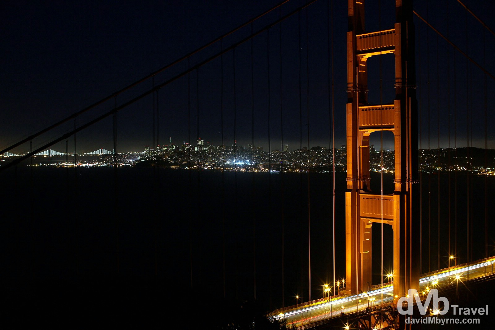 The north pylon of the Golden Gate Bridge, the city of San Francisco & the distant lights of the Bay Bridge as seen from Battery Spencer, Marin Headlands, San Francisco, California, USA. April 10th 2013.
