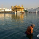 Bathing in the Amrit Sarovar (Pool of Nectar) in the Golden Temple complex, Amritsar, Punjab, India. October 9th 2012.