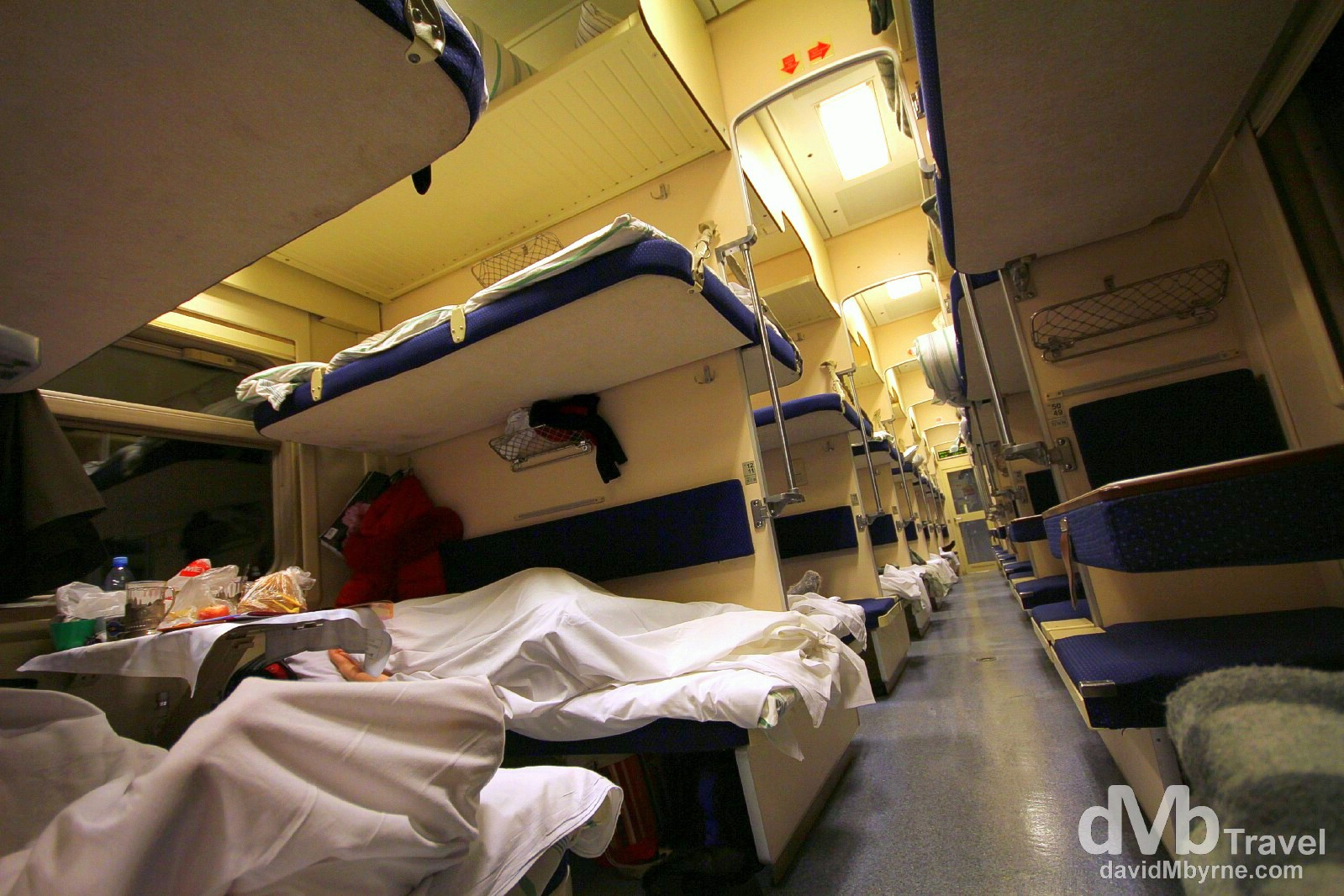 Inside the sparsely populated 3rd class/platzkart carriage number 2 of train 037. 3rd class/platzkart is an open-plan dormitory car with 54 bunks per carriage arranged in open compartments of 4 berths - 2 up/2 down - on one side (left of the picture) and 2 berths - 1 up/1 down - along the carriage wall on the other side of the aisle (right of the picture). Perfect for the budget-conscious traveller; the fare for this 48 hour+, 3,215 kilometre trip, was 3,900 roubles (€100). This carriage is new and half empty, which probably explains why I'm still all alone in my 4 berth compartment. On the train from Tomsk to Nizhny Novgorod, Russia. November 12th 2012.