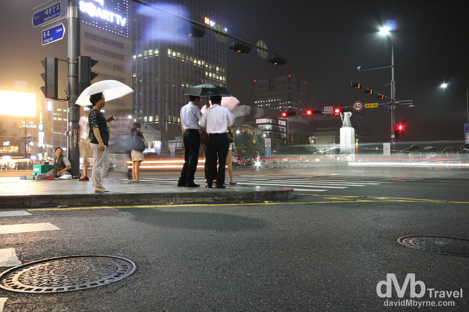 Waiting in the light rain at a traffic junction in Jongno, Seoul, South Korea. July 12th 2012.