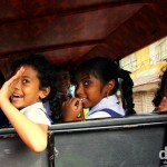 Smiles & waves out the back of a tuk tuk on Bazaar Road in Forth Cochin, Kerala, India. September 18th 2012.