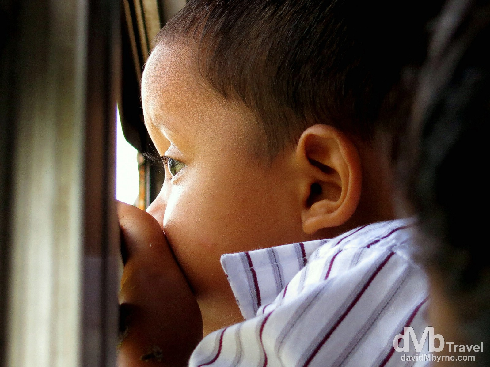 A boy looking out the window on the bus to the ferry terminal in Isla de la Ometepe, Lago de Nicaragua, Nicaragua. June 21st 2013.