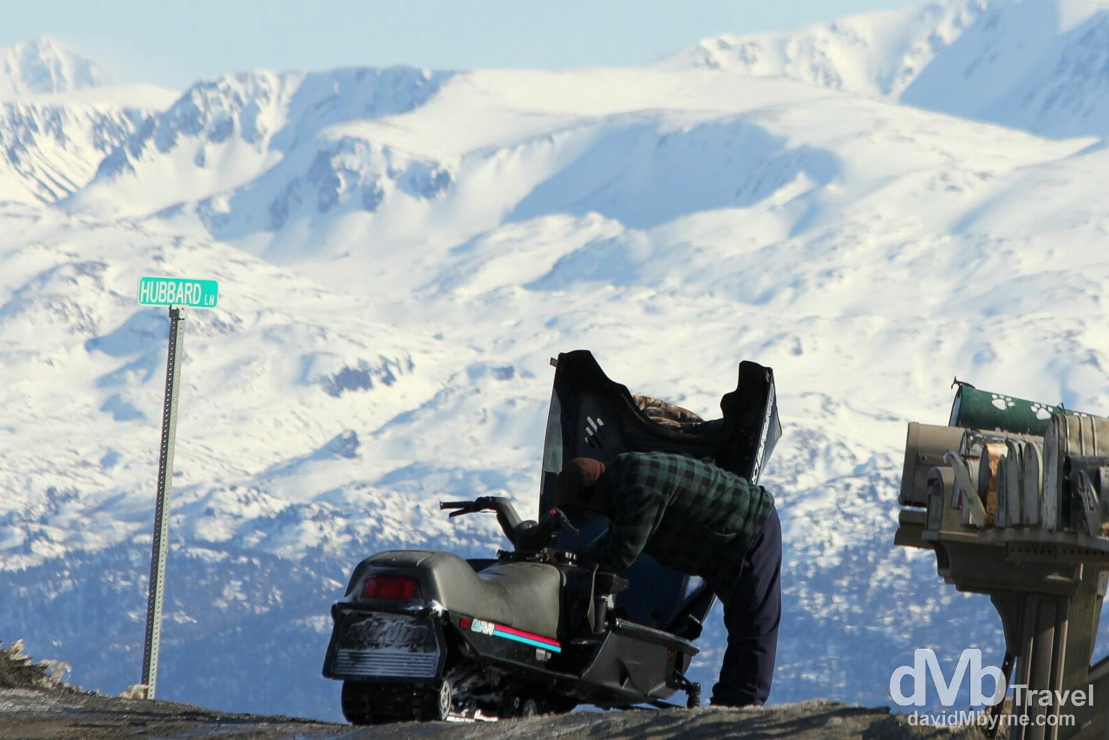 Tending to a snowmobile near Hubbard Lane on Skyline Drive, Homer, Kenai Peninsula, Alaska, USA. March 17th 2013.