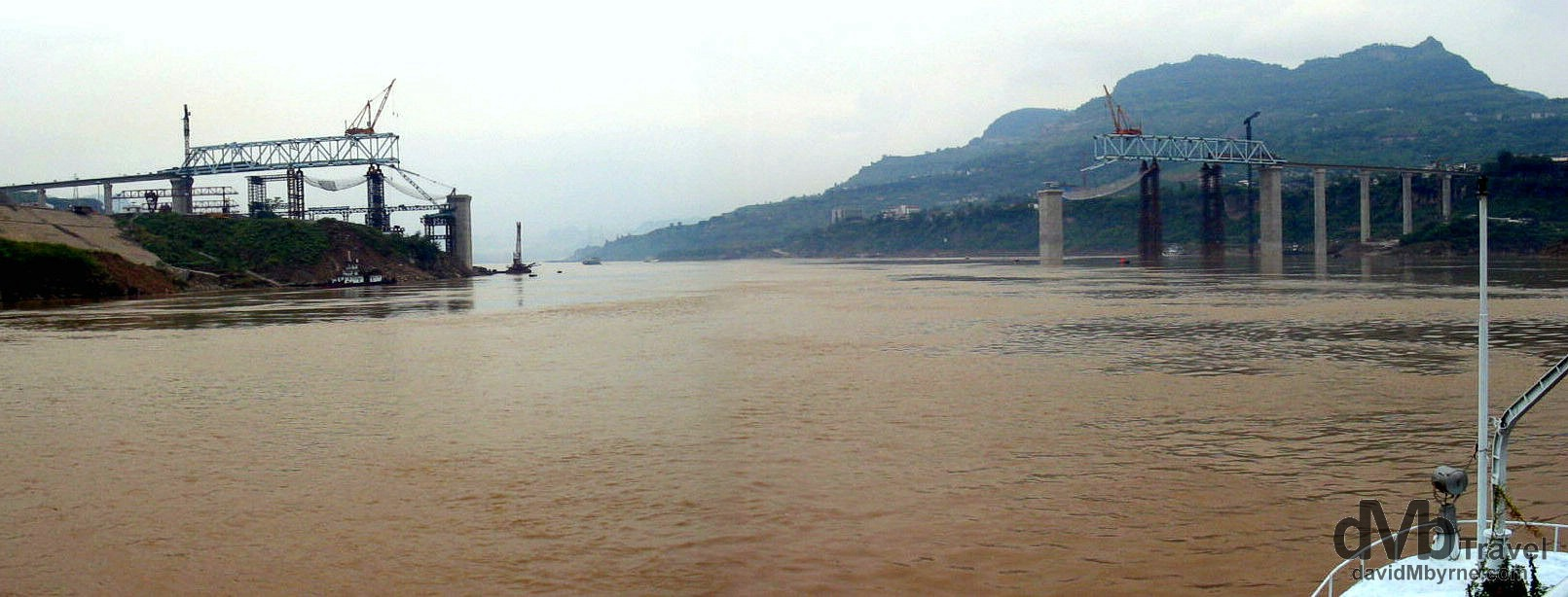 The construction of a bridge spanning the Yangtze River as seen from the river near Wan Xian, central China. September 26th, 2004.