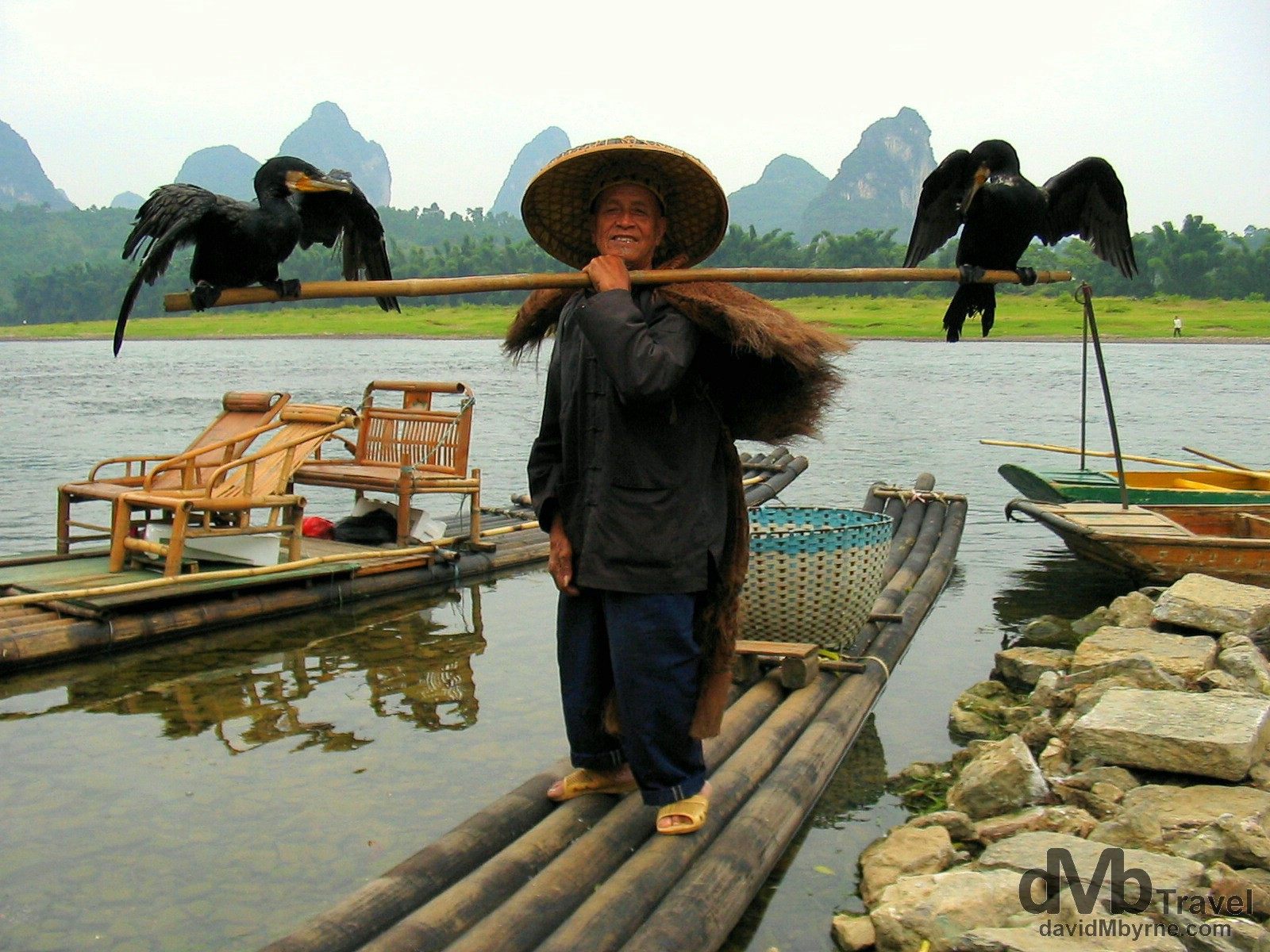 A Cormorant fisherman poses for a picture by the banks of the Li river in Yangshuo, Guangxi Province, Southern China. September 10th, 2004.