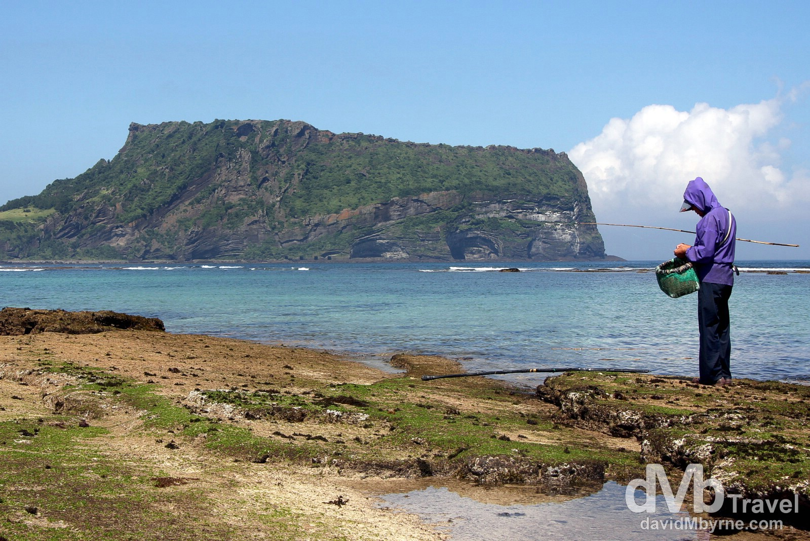 A fisherman fishes the waters near Seongsan Ilchubong (Sunrise Peak) on Jeju-do, South Korea. July 16th, 2011