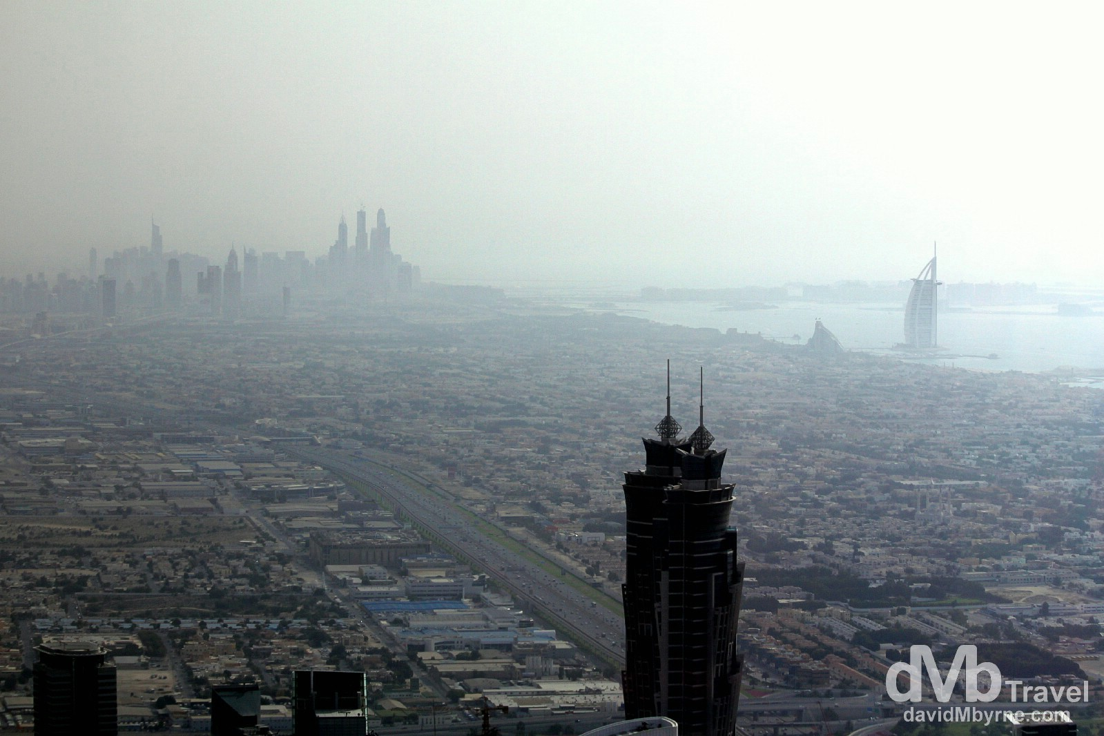 The distant towers of Dubai Marina, the man-made Palm Jumeirah island & the 7-star Burj Al Arab as seen from the At The Top, the 124th floor viewing deck of the Burj Khalifa, the world's tallest building. Dubai, UAE. April 18th, 2014.