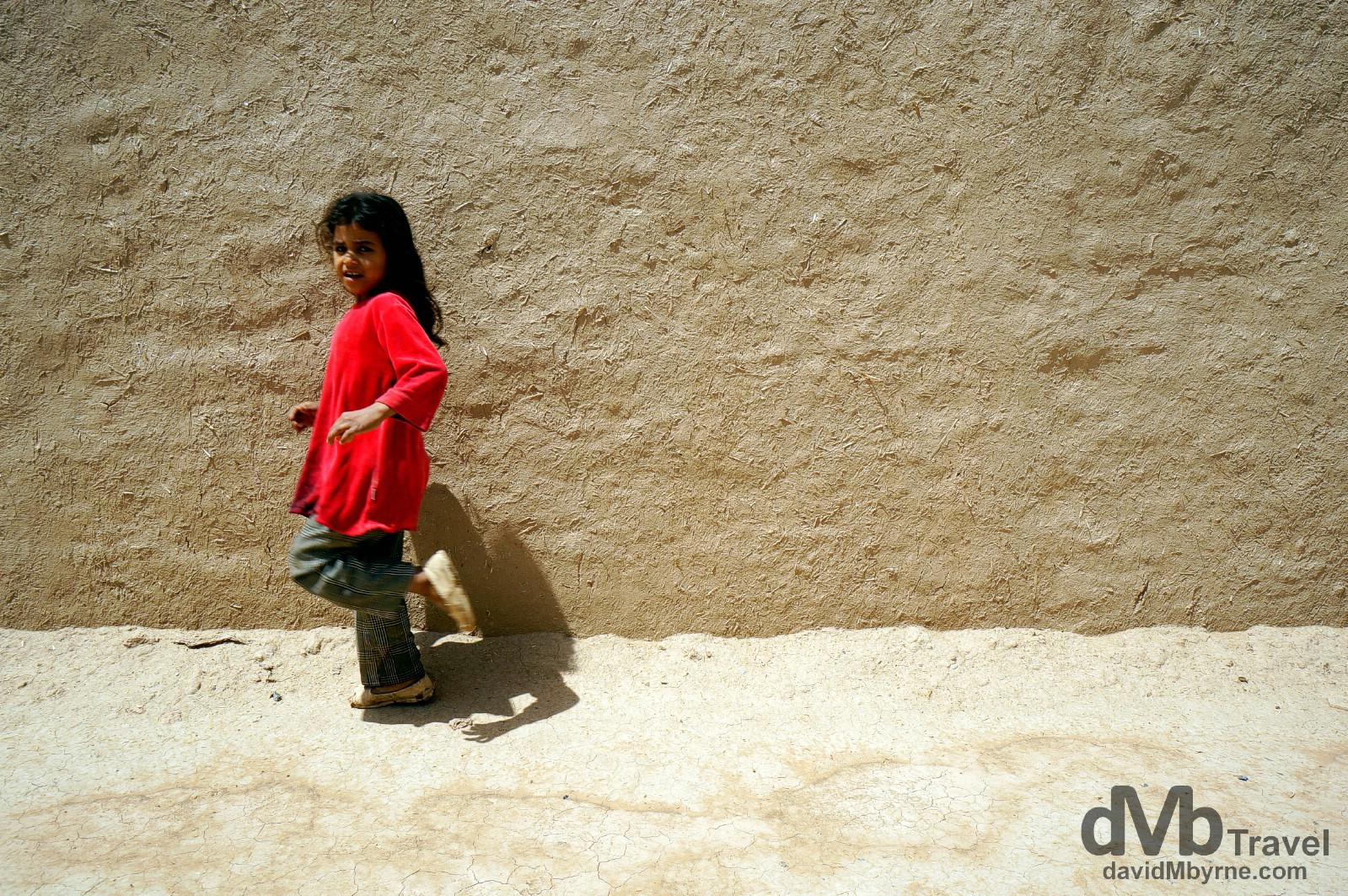 Walking by the pise (mud & rubble building material) walls of Ksar Oualad Abdelhalim, Rissani, Morocco. May 22nd, 2014.