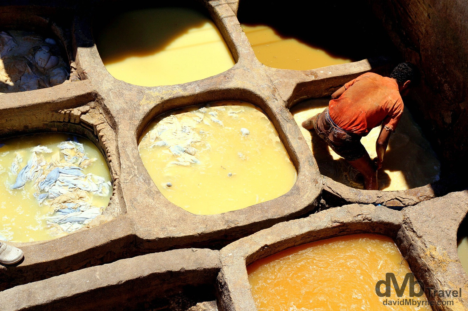A worker in one of the pits of the Tanneries Chouwara, Fes el Bali, Fes, Morocco. May 29th, 2014.