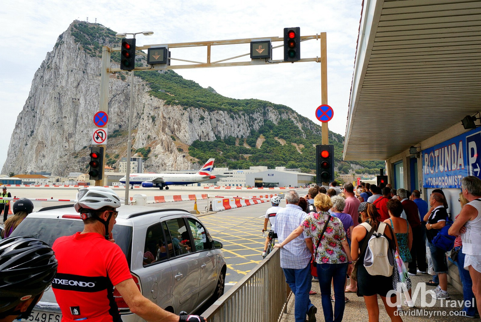 Pedestrians waiting for an arriving BA plane to taxi to its gate to enable passage across the runway of the International Airport in Gibraltar. June 5th, 2014.