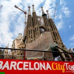 A City Tour bus passing the Passion Facade of the Sagrada Família in Barcelona, Catalonia, Spain. June 17th, 2014.