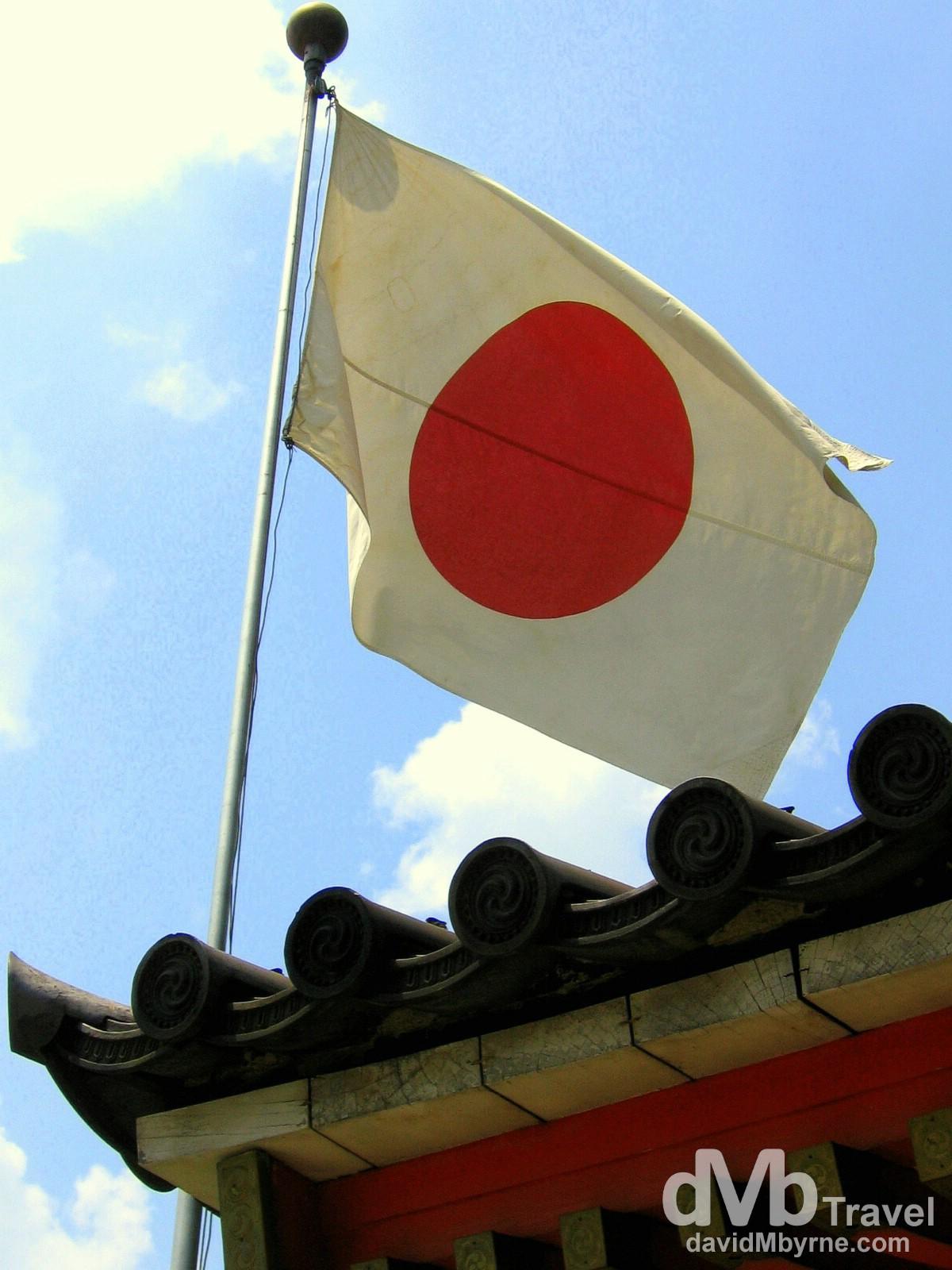 The Japanese flag flies over the entrance to the Yasaka Jinja Shrine in Kyoto, Honshu, Japan. July 18th, 2005.