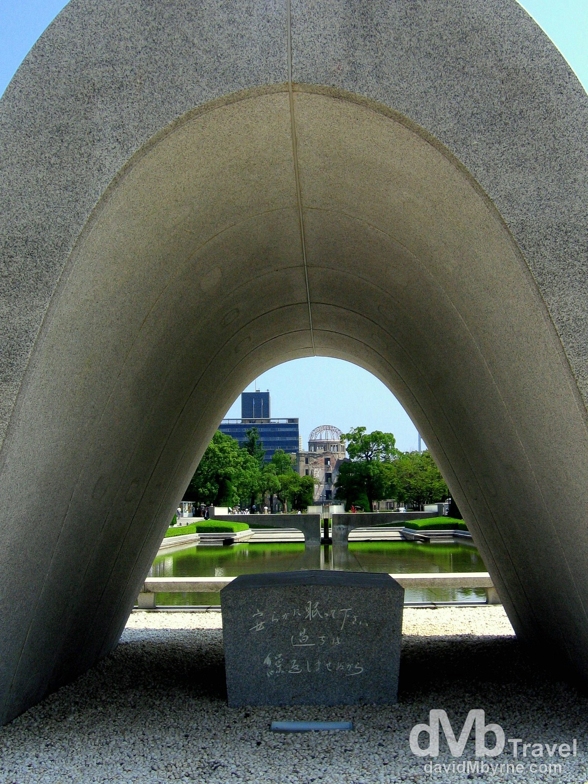The distant A-bomb Dome as seen from under the arch of the Memorial Cenotaph in Hiroshima Peace Memorial Park, Hiroshima, Honshu, Japan. July 22nd, 2005.