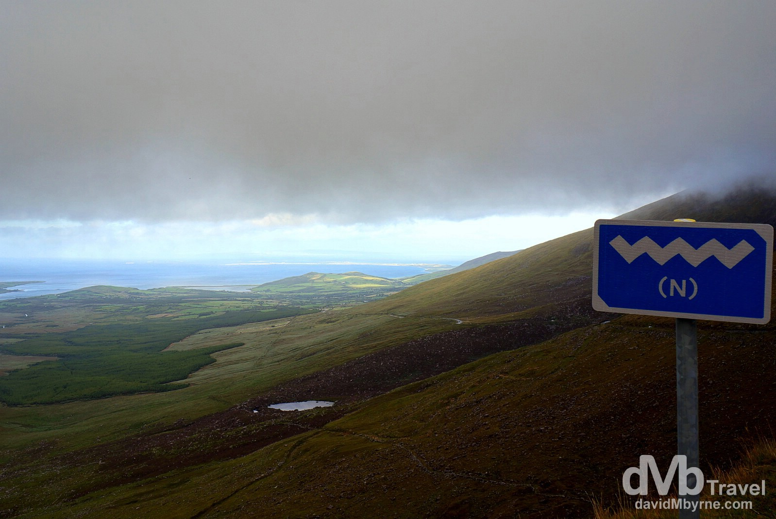 Wild Atlantic Way signage & ominous clouds hanging over the Conor Pass, the highest mountain pass in Ireland. Dingle Peninsula, Co. Kerry, Ireland. August 27, 2014.