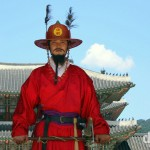A ceremonial guard standing under the South Gate (Gwanghwamun) of Gyeongbok Palace, the largest & most important of the restored royal palaces in Seoul, South Korea. July 8, 2008.