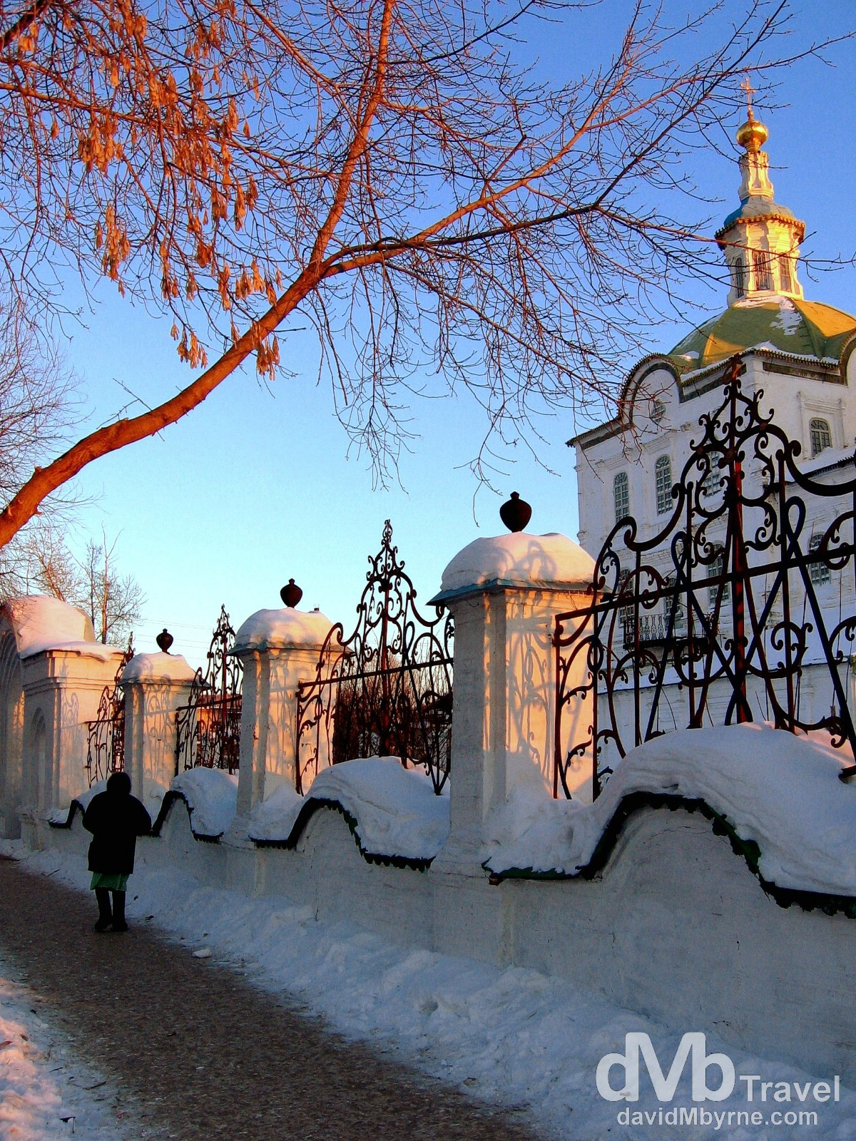 Walking on the icy paths at sunset outside the Mikhail Arkhangel Church, Old Town Tobolsk, Siberian Russia. February 22, 2006.