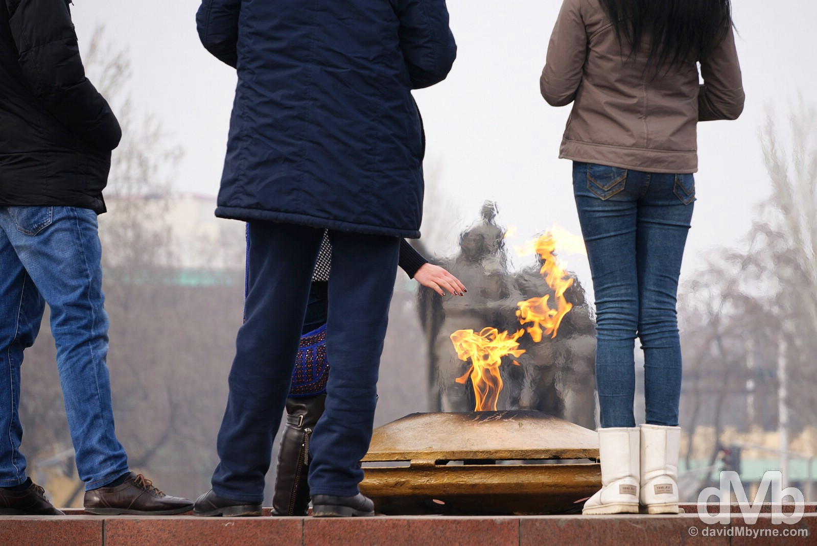 Warming up by the Eternal Flame of the War Memorial in Victory Square, Bishkek, Kyrgyzstan. February 23, 2015.