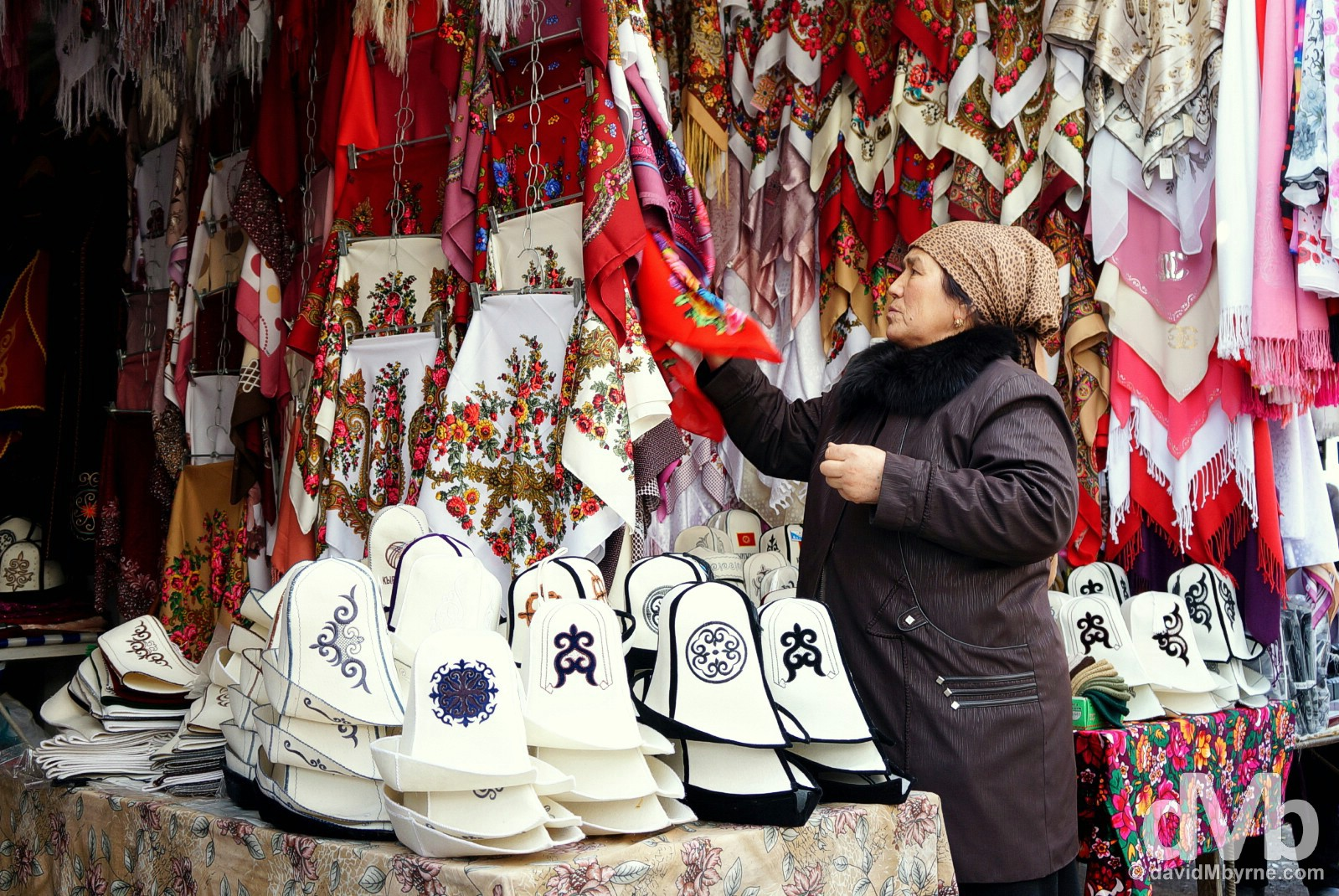 Silk scarfs & traditional white ak-kalpak hats on sale at a stall in the bazaar in Osh, southern Kyrgyzstan. March 3, 2015.