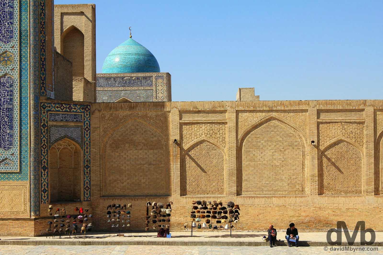 Sitting by the walls of the Kalon Mosque as seen from the Mir-i-Arab Medressa in Bukhara, Uzbekistan. March 12, 2015.