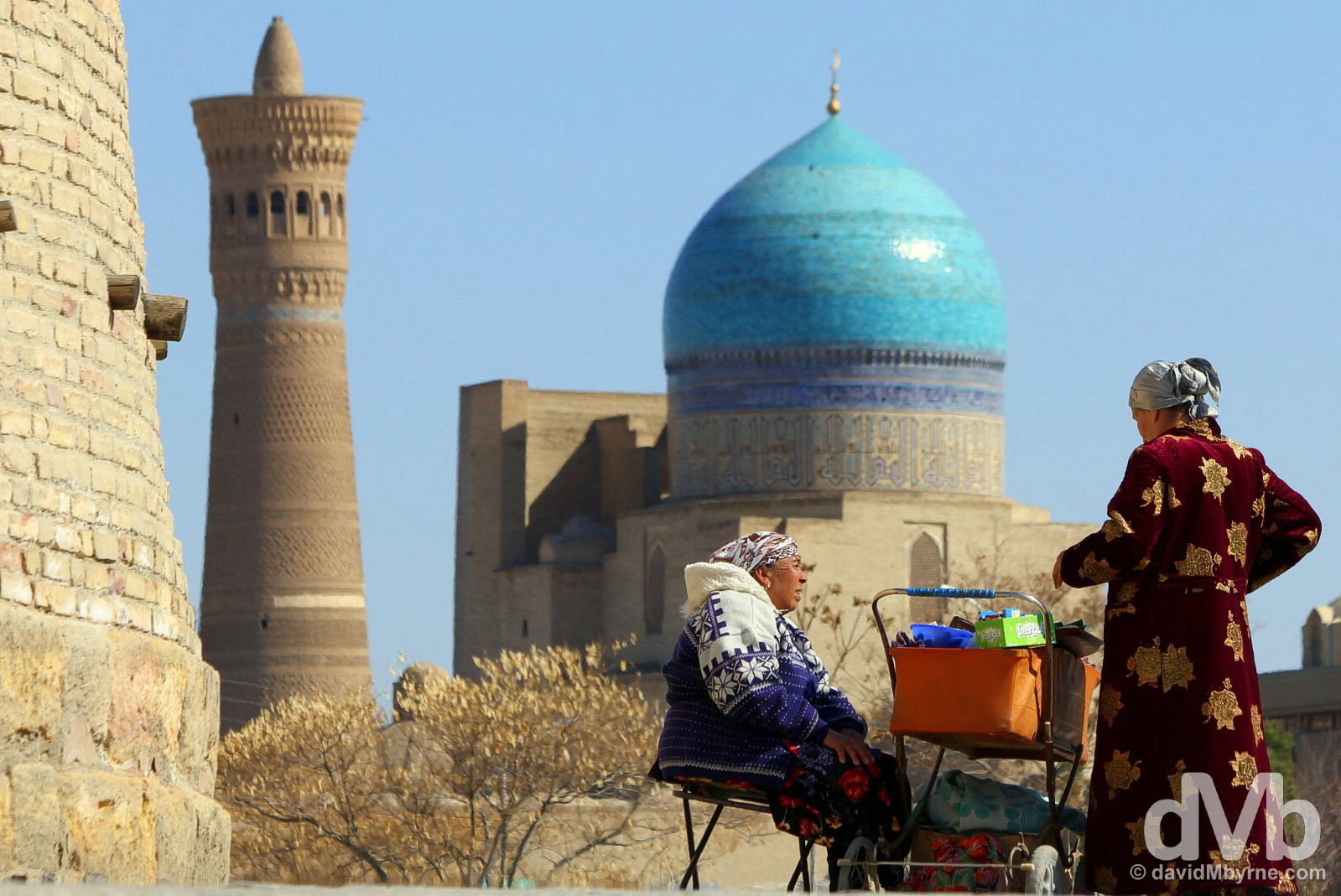 Conducting business by the walls of the Ark in the Registan in view the Kalon Mosque & Minaret. Bukhara, Uzbekistan. March 12, 2015.